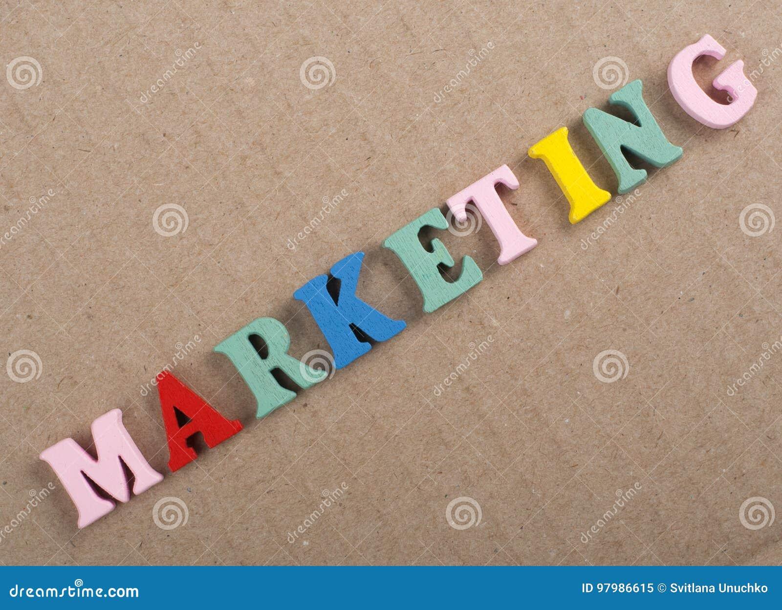 MARKETING-Wort auf dem hölzernen Hintergrund verfasst von den hölzernen Buchstaben des bunten ABC-Alphabetblockes, Kopienraum für
