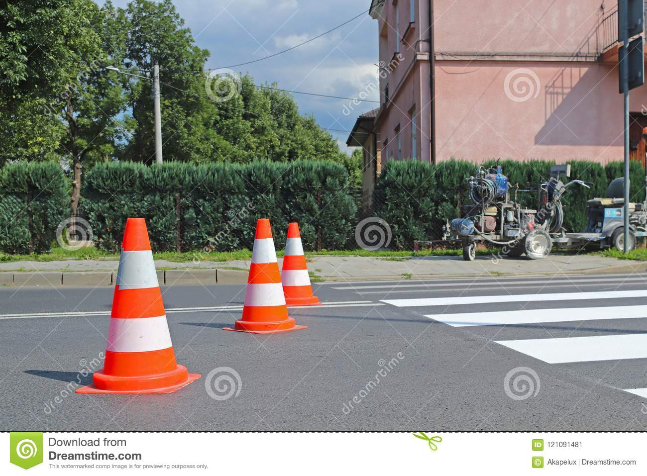 Marking with traffic signs a new colored pedestrian crossing. Restriction of traffic by road signs. A machine for drawing and upda