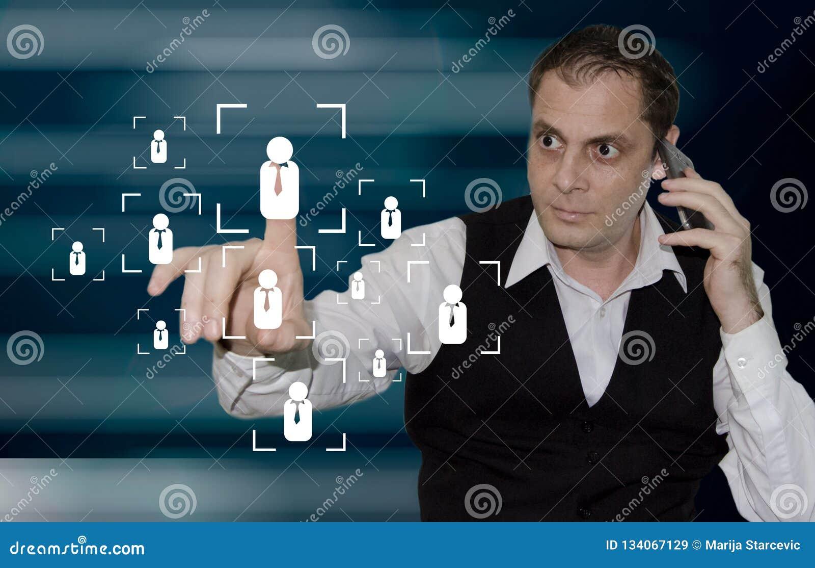 Marknadsföra strategi - affärsman som trycker på personsymbolen på den faktiska skärmen, medan ha telefonkonversation