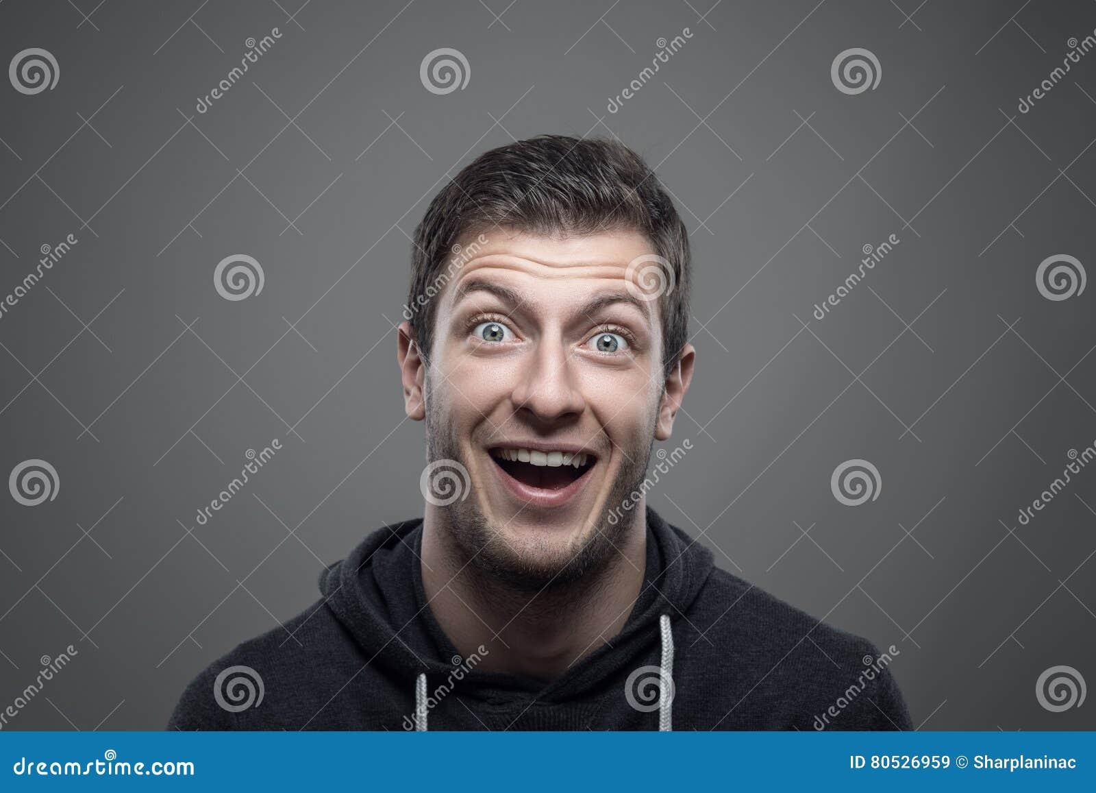 Markotny portret zdziwiony ekspresyjny młody człowiek patrzeje kamerę