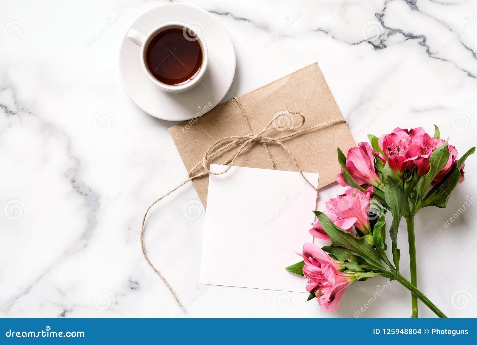 Marmeren bureau met roze bloemen, prentbriefkaar, kraftpapier-envelop, streng, katoenen tak