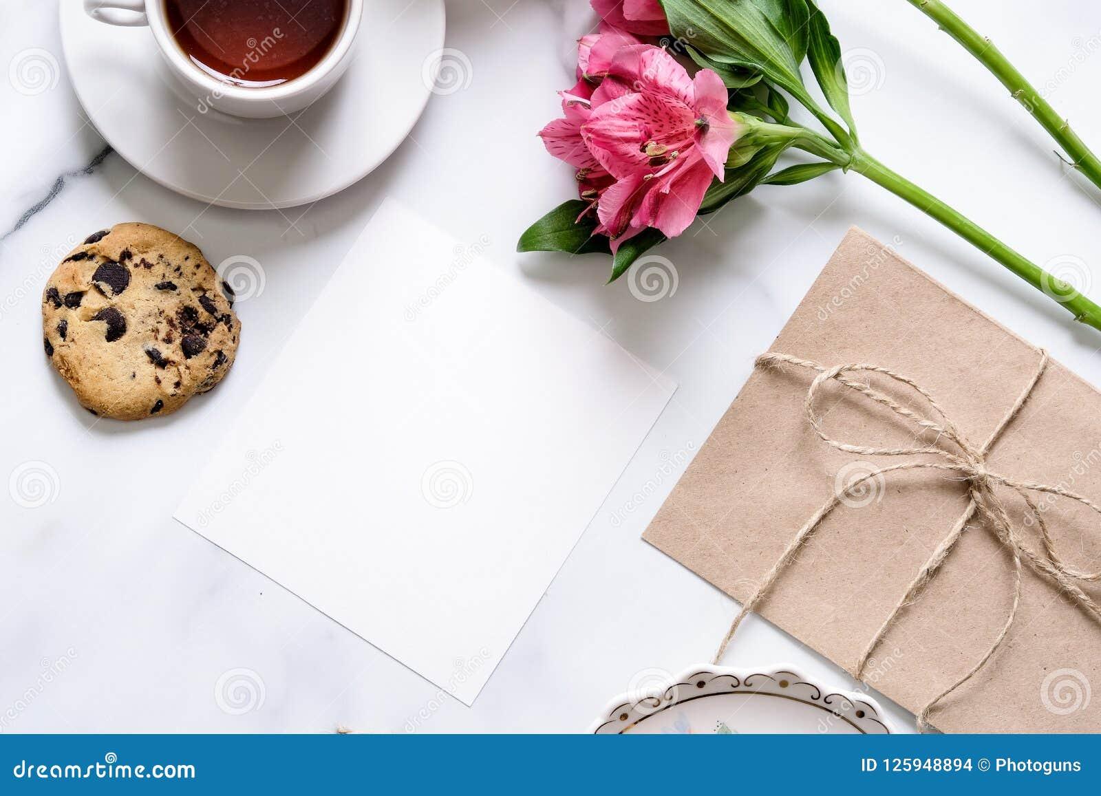 Marmeren bureau met roze bloemen, prentbriefkaar, kraftpapier-envelop, streng, katoenen tak, uitnodigingskaart met exemplaarruimt