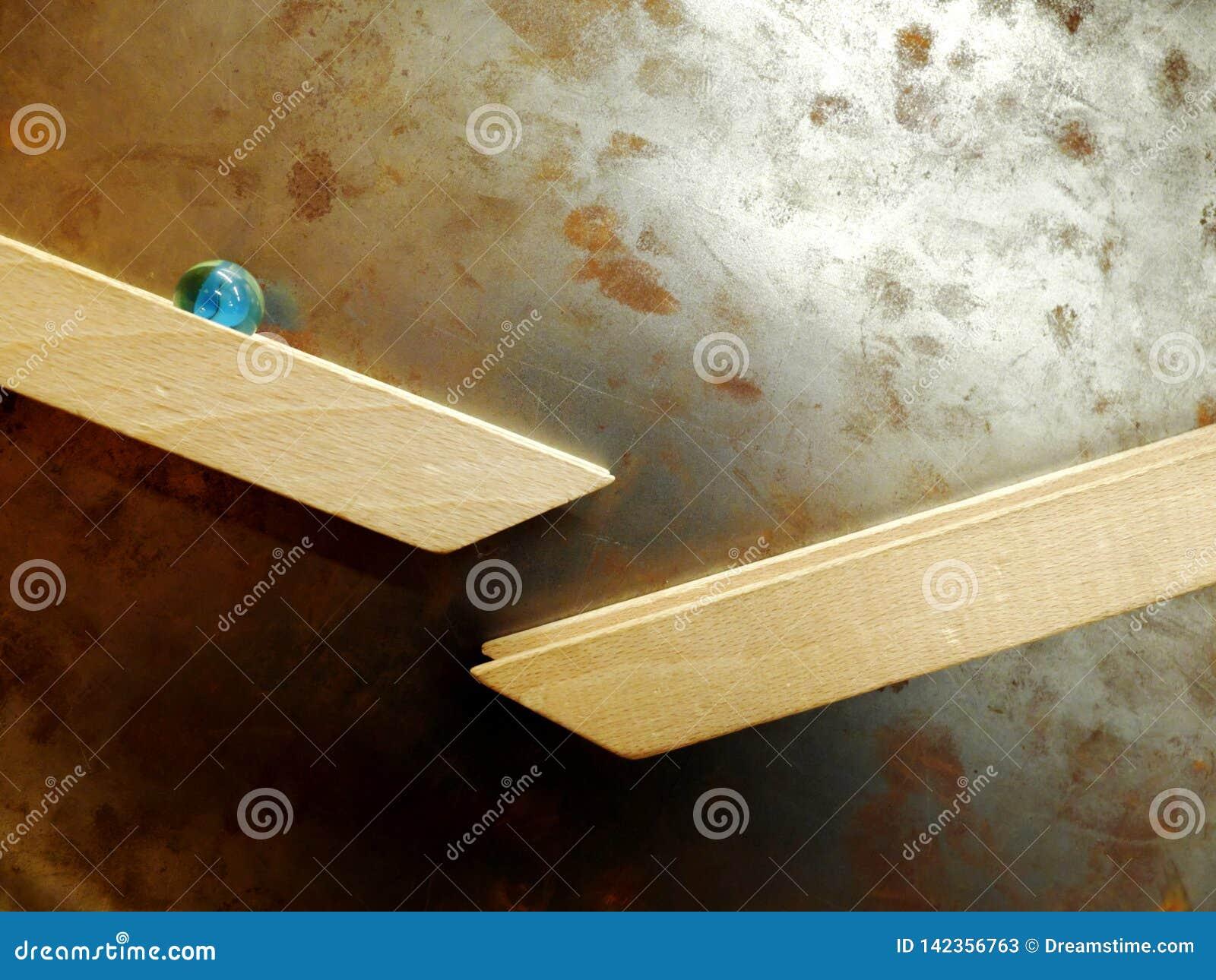 Marmorboll som ner rullar längs trästången som fästas magnetiskt till den rostiga väggen för metall Begreppet av nedåtriktad röre