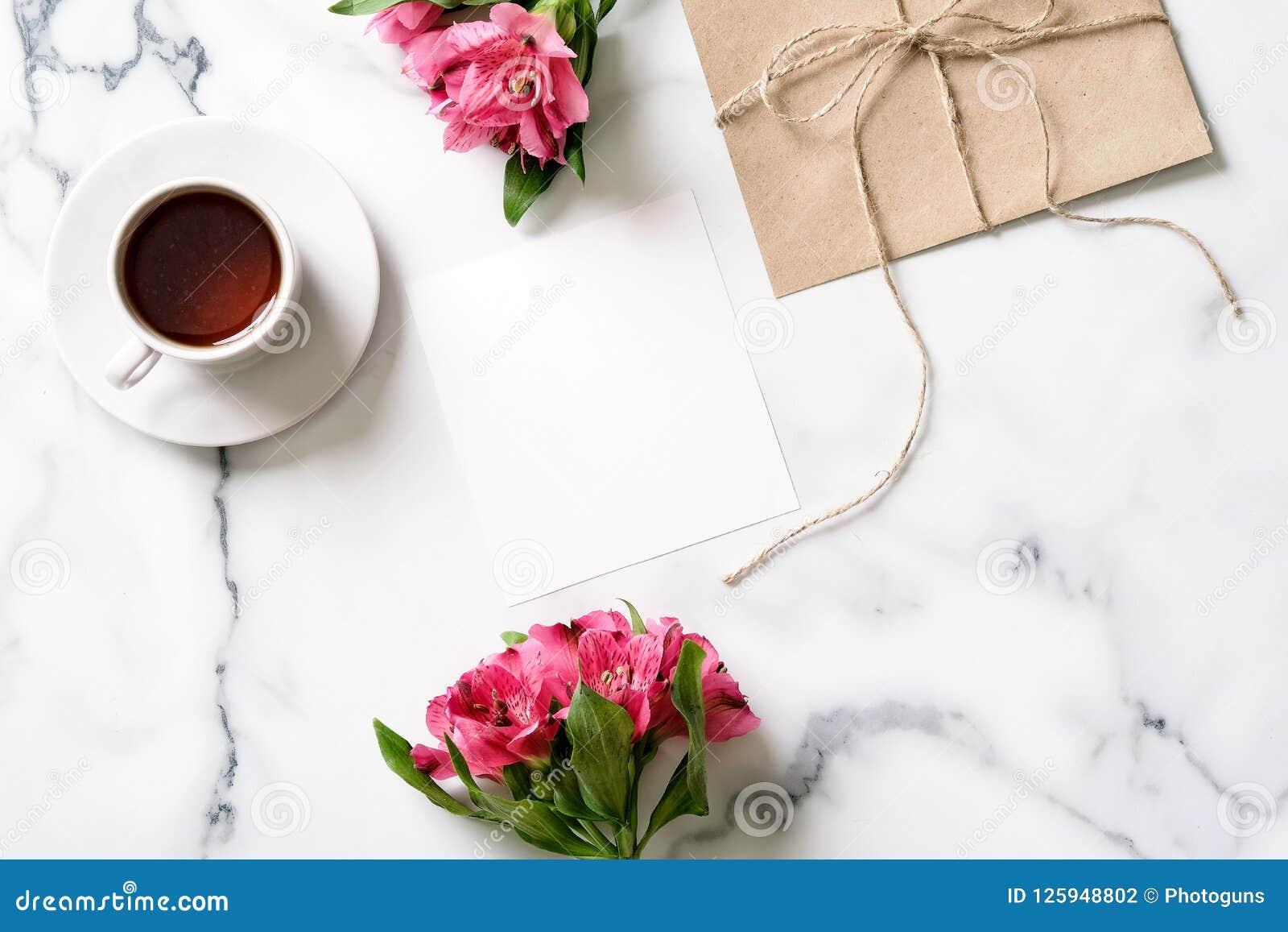 Marmorskrivbordet med rosa färger blommar, vykortet, det kraft kuvertet, tvinnar, bomullsfilialen