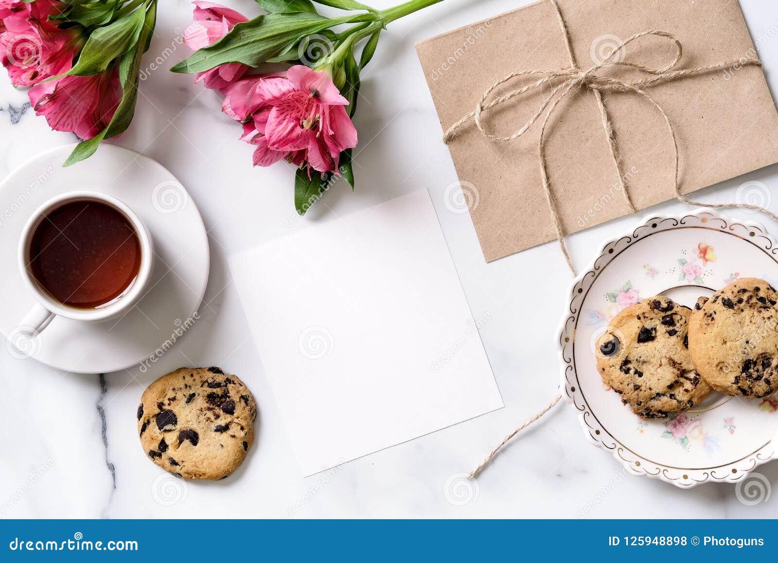 Marmorskrivbordet med rosa färger blommar, vykortet, det kraft kuvertet, tvinnar, bomullsfilialen, inbjudankort med kopieringsutr