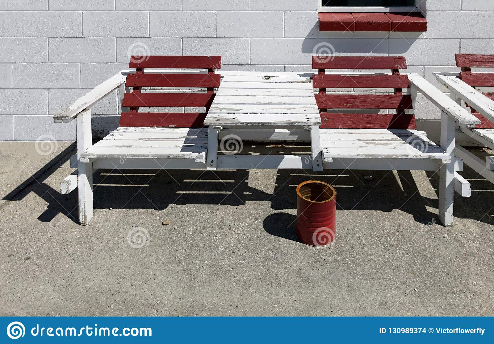 Maroon and white color painted wooden outdoor summer bench chair against white brick concrete block wall background and red bucket