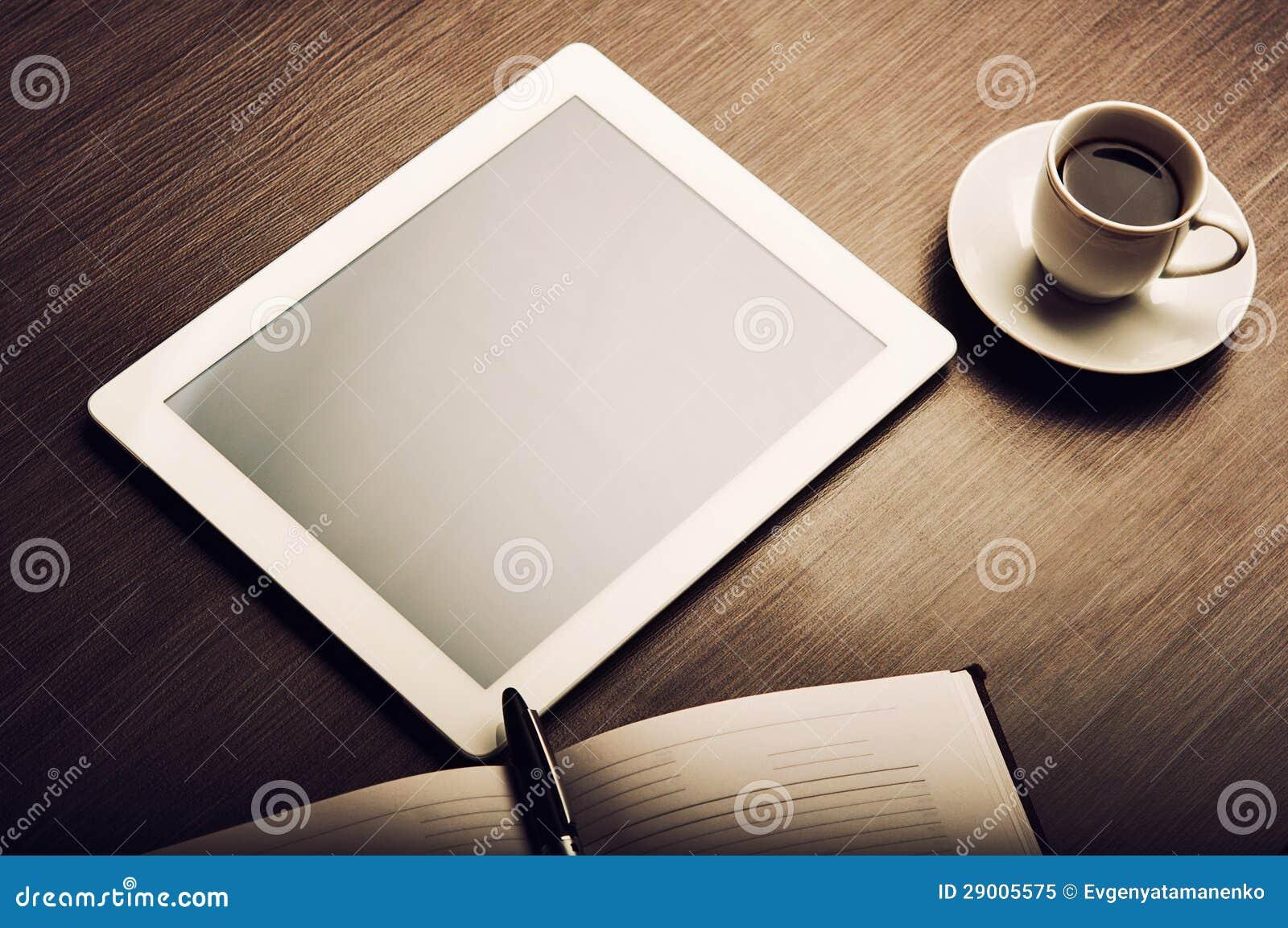 Marque o PC e um café e um caderno com a pena na mesa de escritório