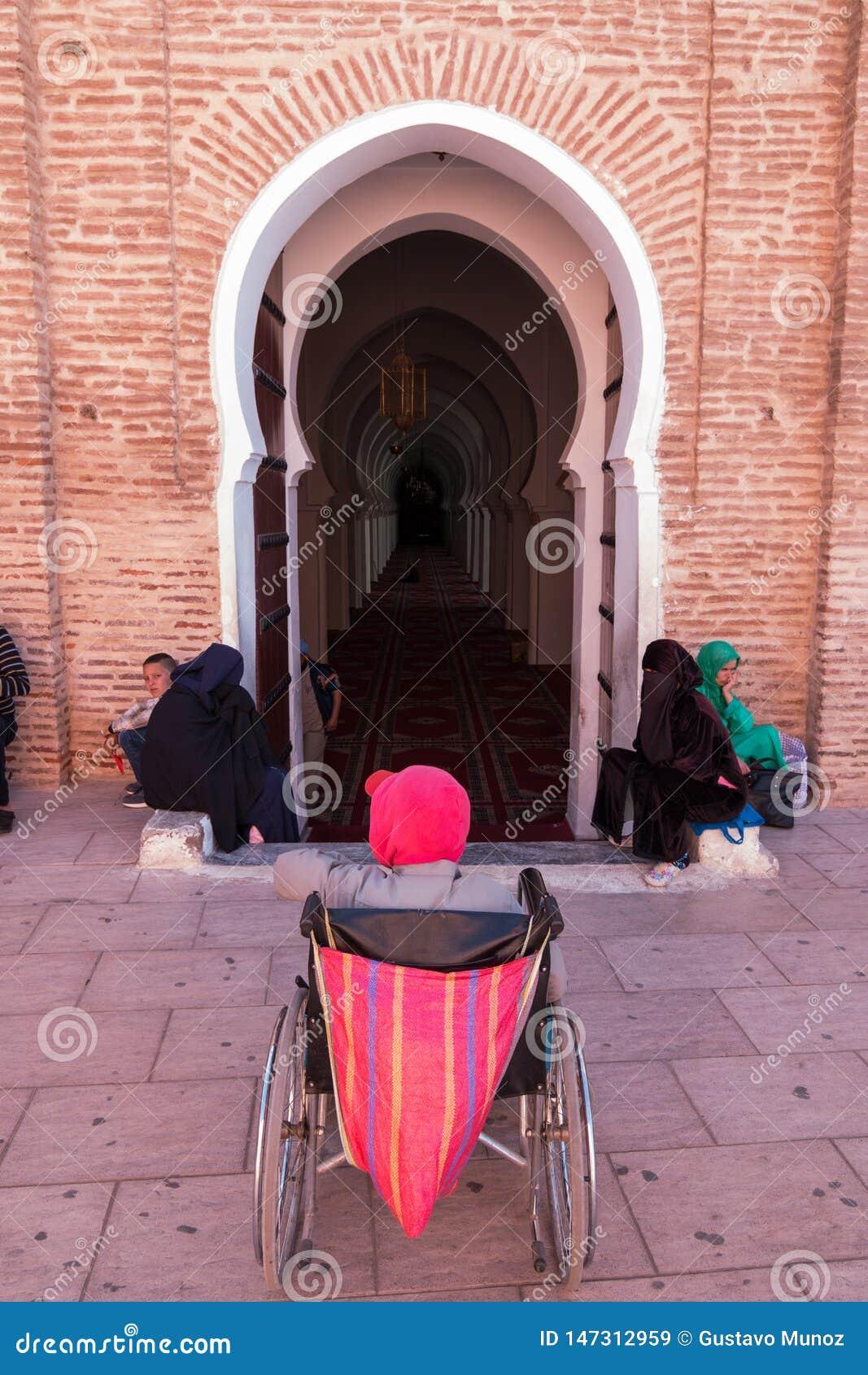 Marrakesh, Marocco - 13 marzo 2018: Un uomo nelle attese di una sedia a rotelle all entrata della moschea di Koutoubia affinchè q