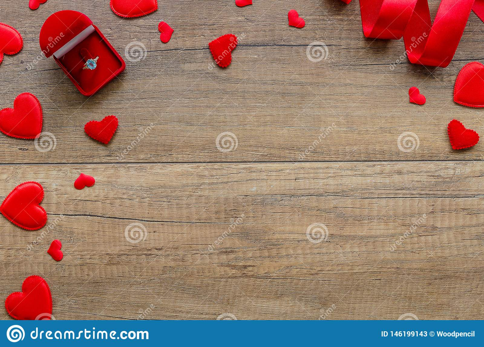 Marriage proposal and engagement concept with romantic arrangement felt red hearts, and ring box on wooden background