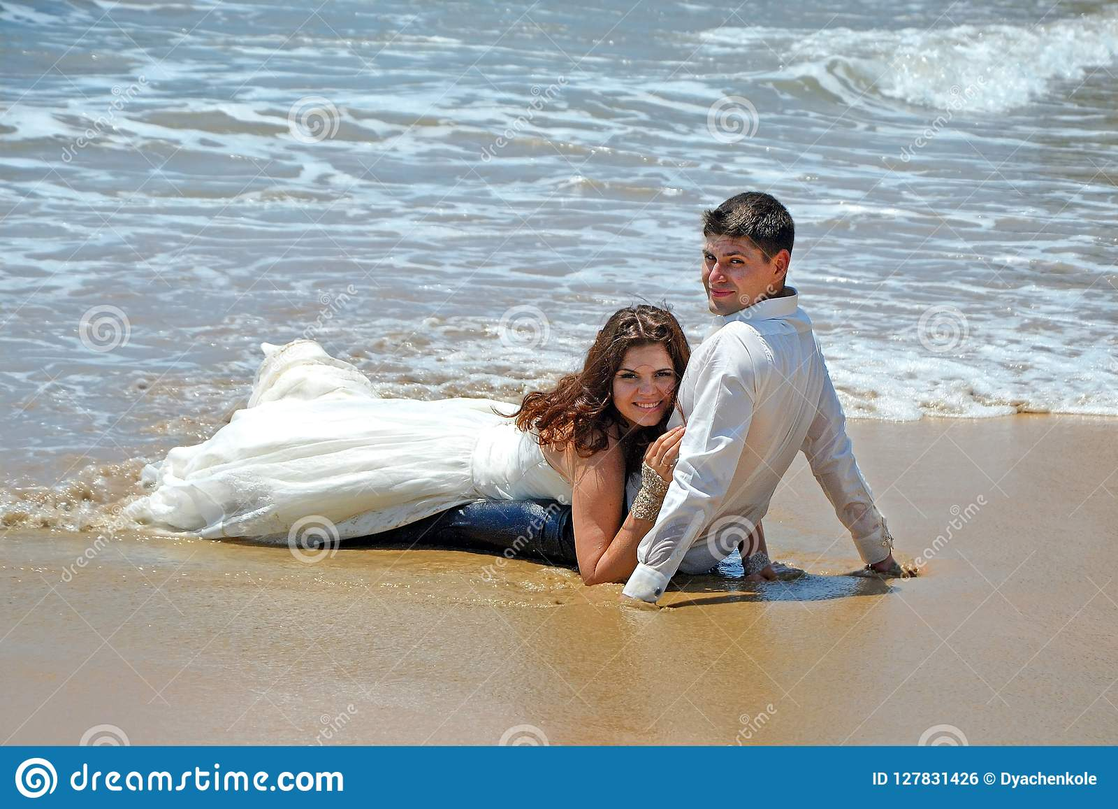 A married couple is lying on the sand on the beach of the Indian Ocean. Wedding and honeymoon in the tropics on the island