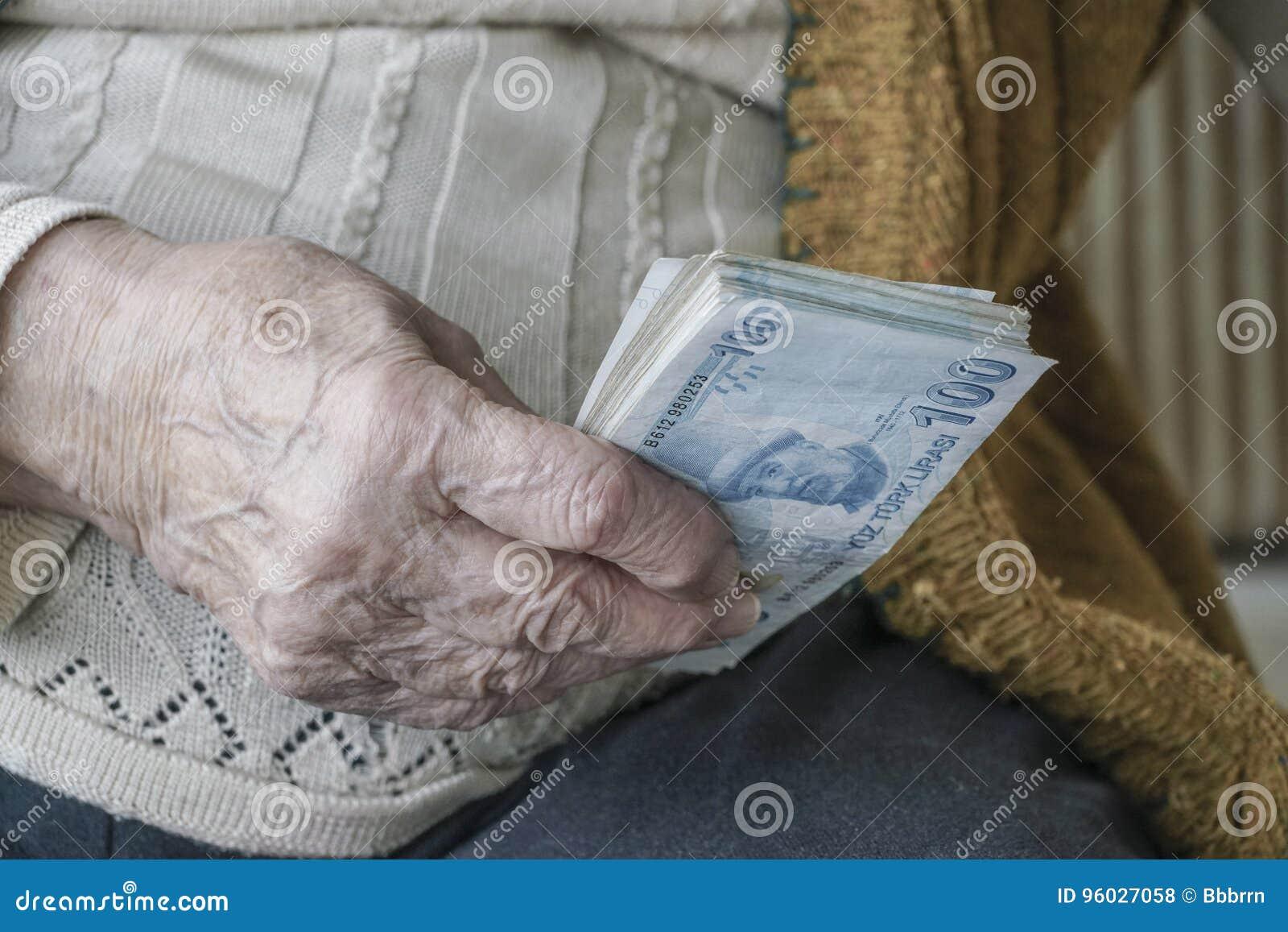 Marszcząca ręka trzyma Tureckiego lira banknoty