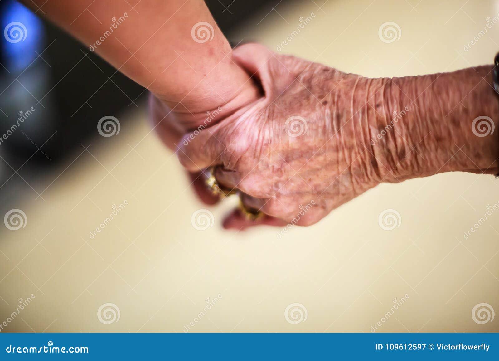 Marszcząca starsza kobiety ` s ręka trzyma młodego człowieka ` s ręka, chodzi w zakupy centrum handlowym Rodzinny powiązanie, zdr