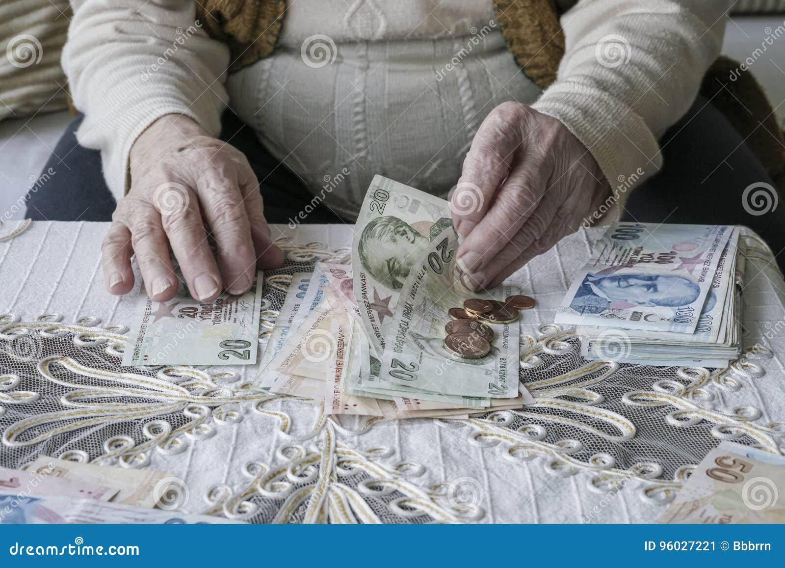 Marszczyć ręki liczy Tureckiego lira banknoty