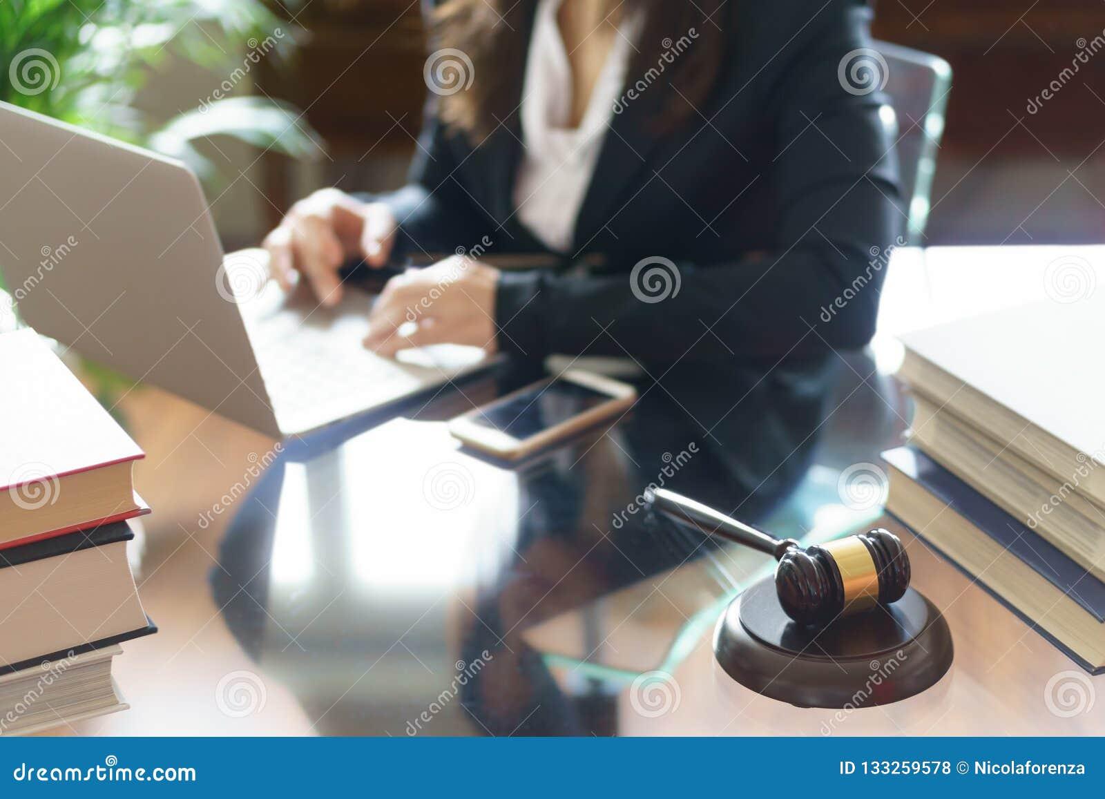 Marteau et avocat de juge travaillant sur un ordinateur portable dans le bureau