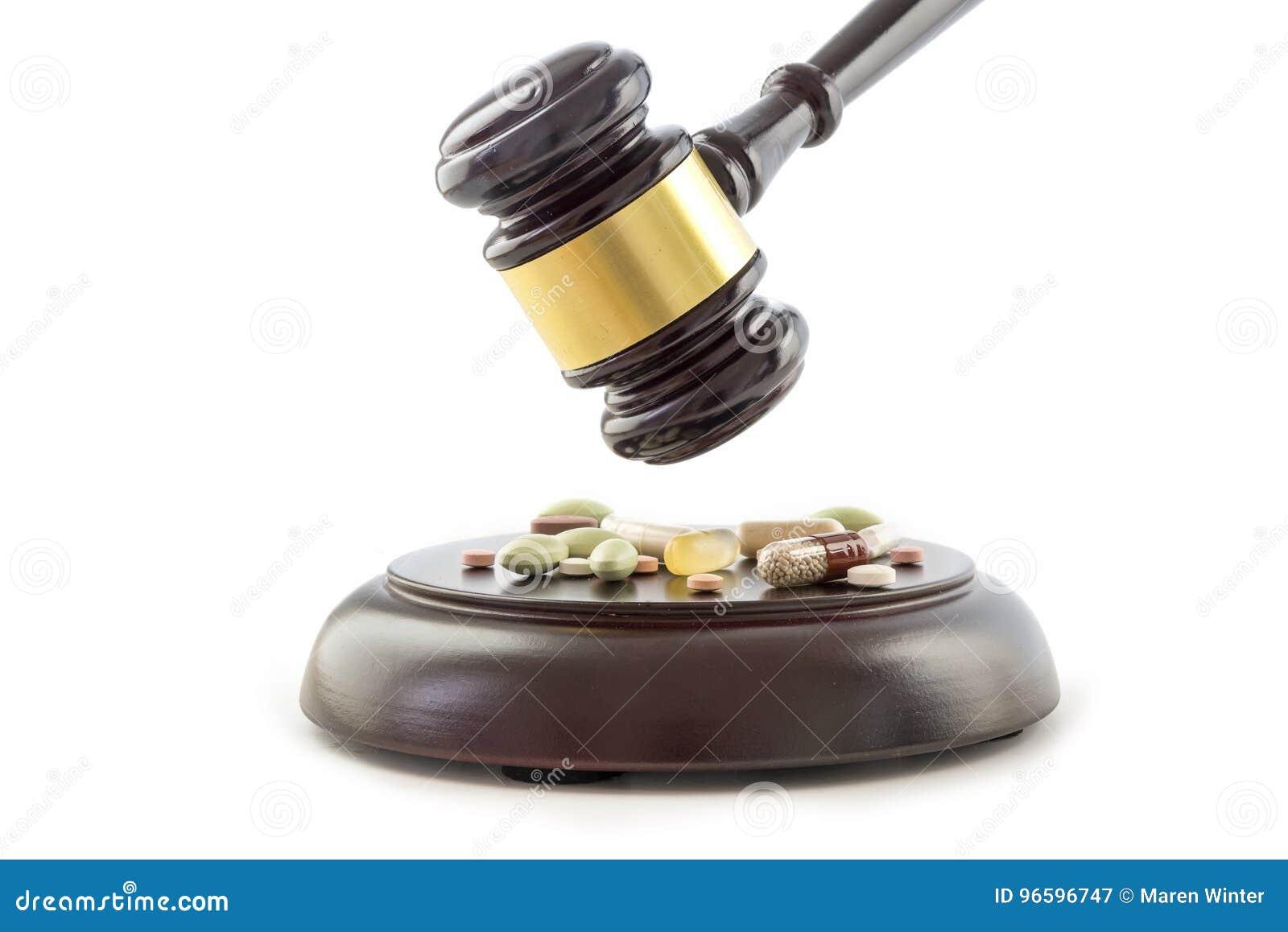 Marteau et drogues de loi, comprimés et pilules sur le bloc sain en bois