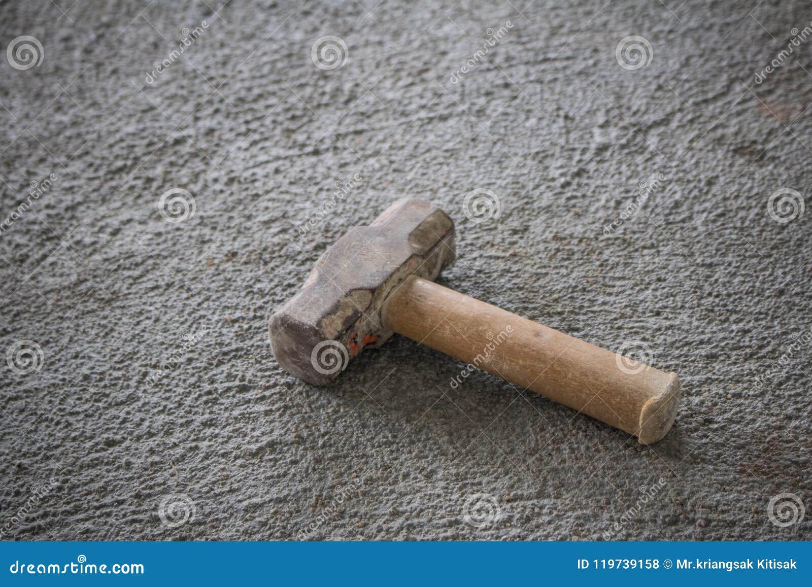 Marteau sur le plancher de ciment pour la construction