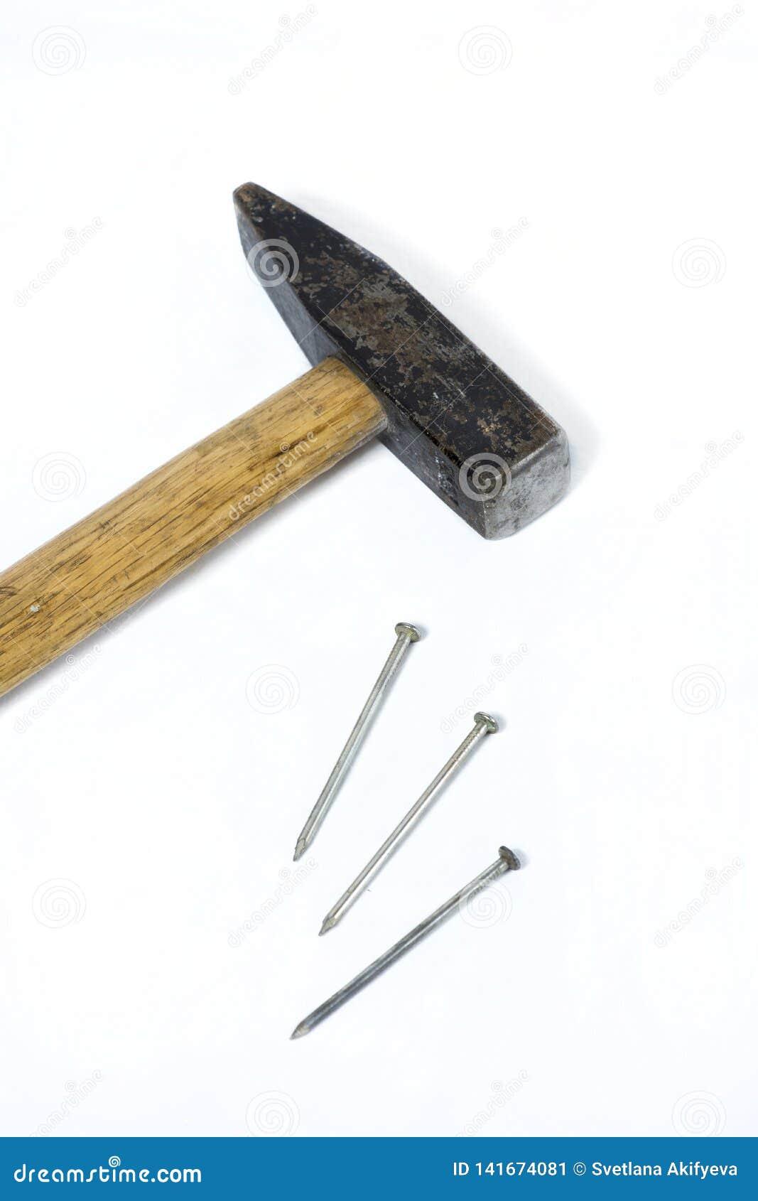 Martelo do ferro com o punho de madeira com os pregos no fundo branco