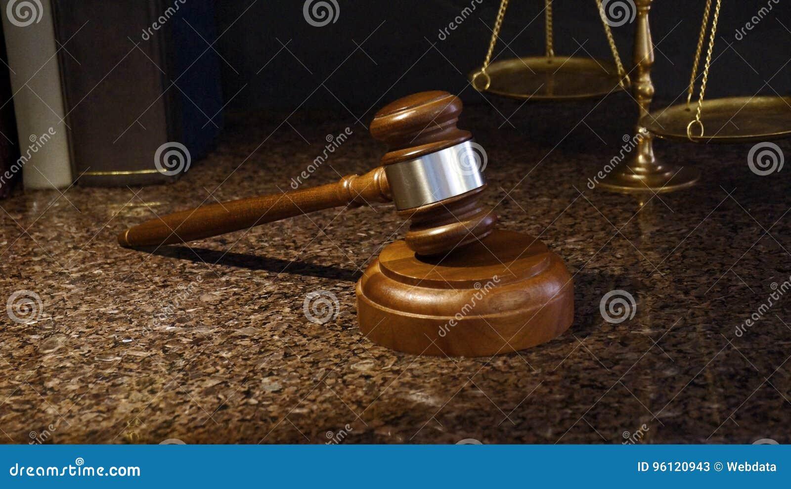 Martelo, escalas de justiça e livros de lei no mármore