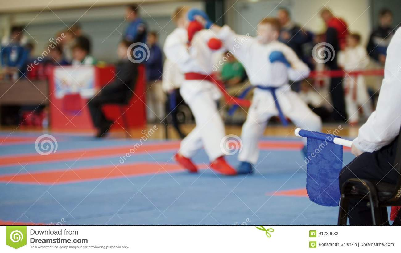 Martial art competitions - coach-judge with blue flag looking at karate teenager`s fighting