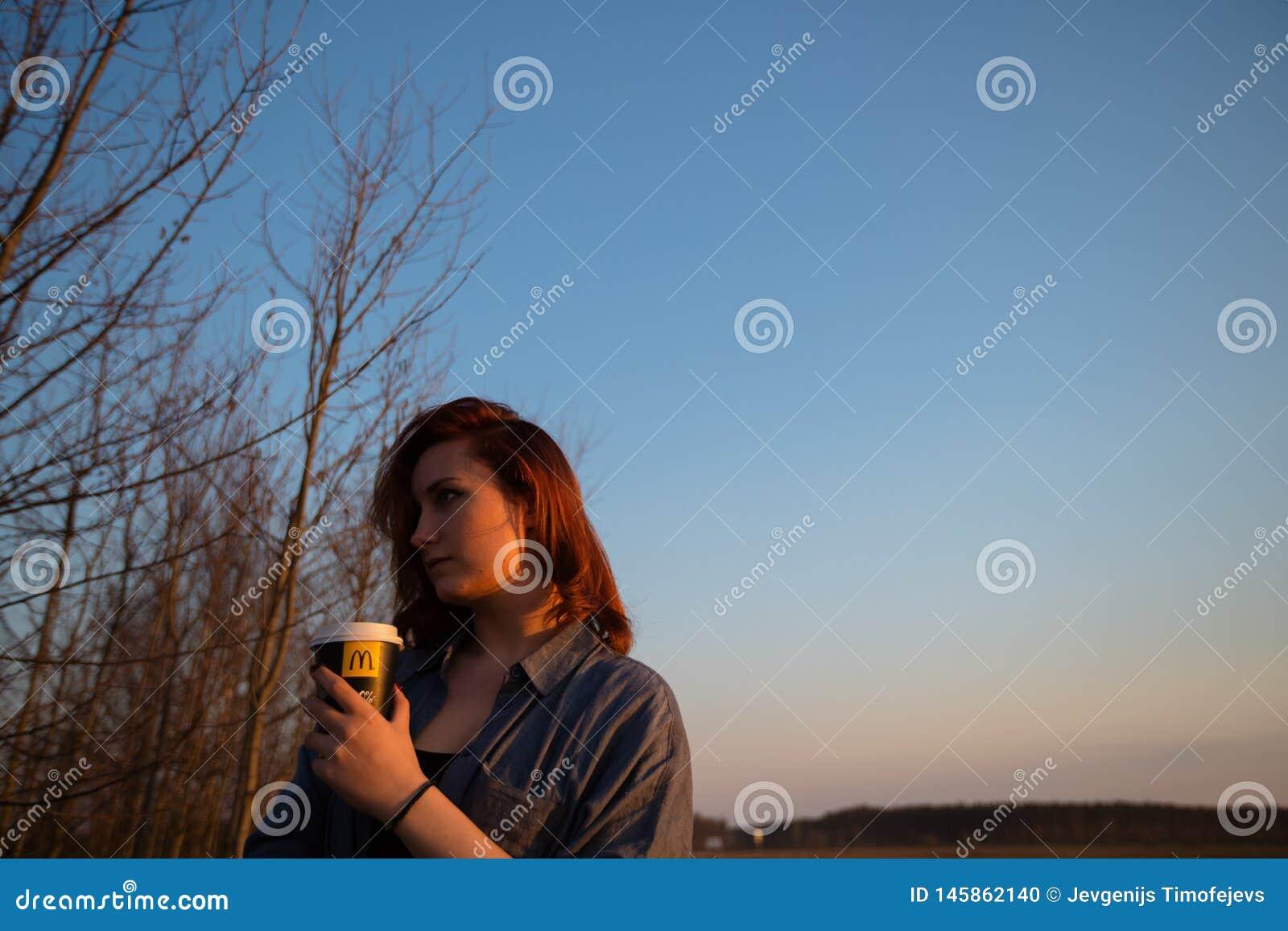 MARUPE, LETTONIE - 22 AVRIL 2019 : Jeune femme buvant du caf? de McDonalds dehors dans un domaine pendant le coucher du soleil