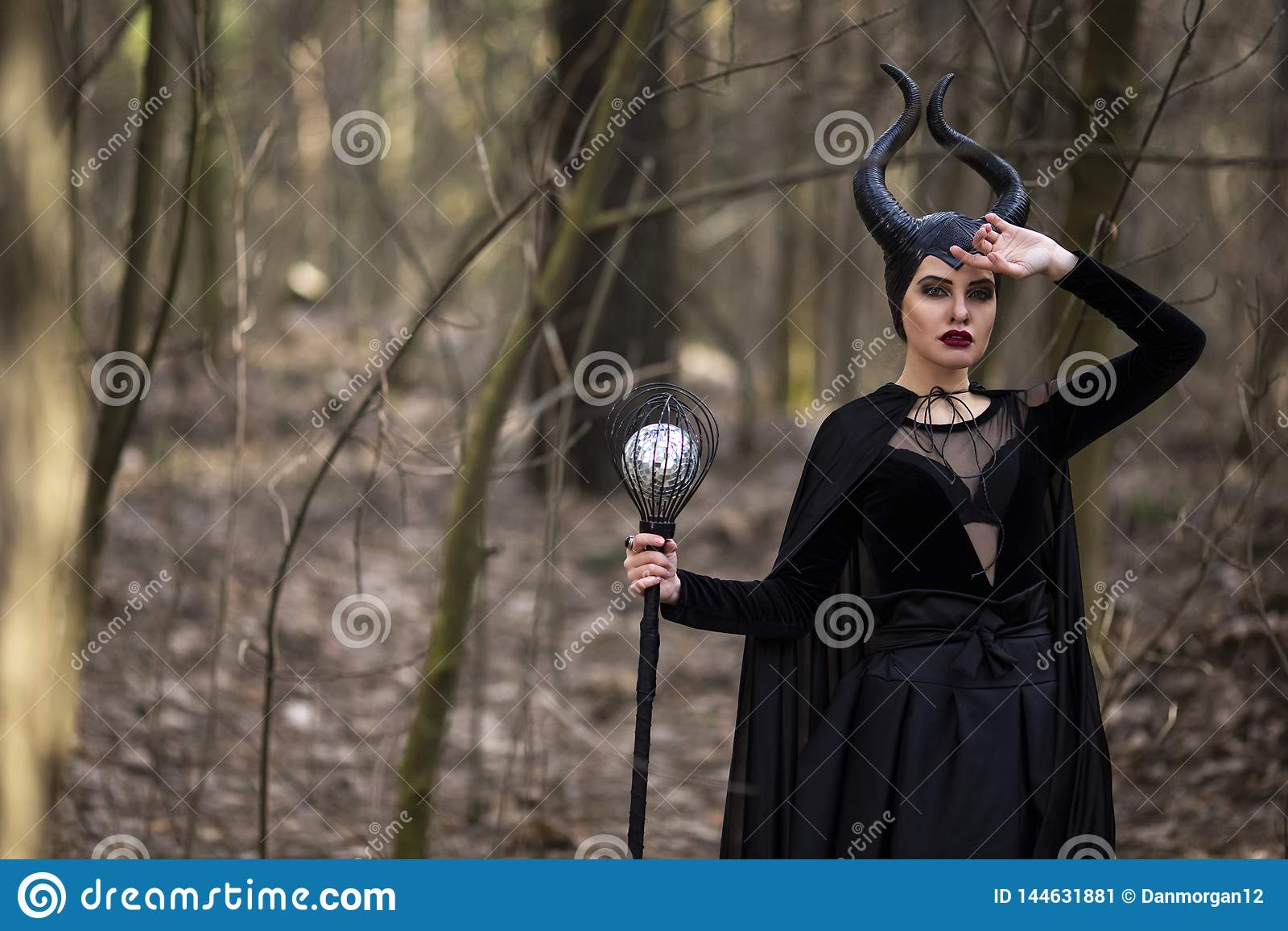 Marvellous and Magical Maleficent Woman with Horns Posing in Spring Empty Forest with Crook