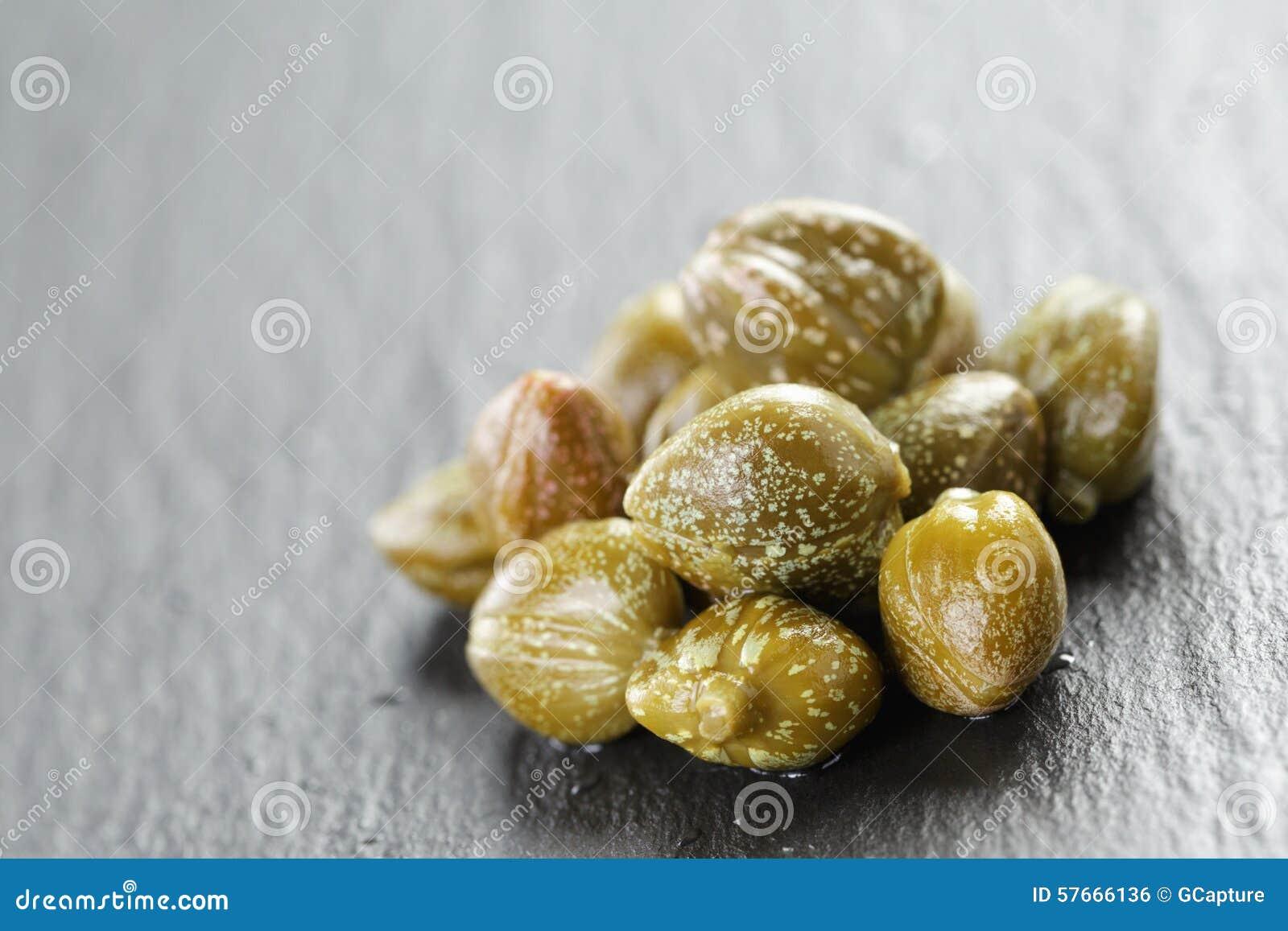 Marynowani kapary w oliwnym pucharze na łupku wsiadają