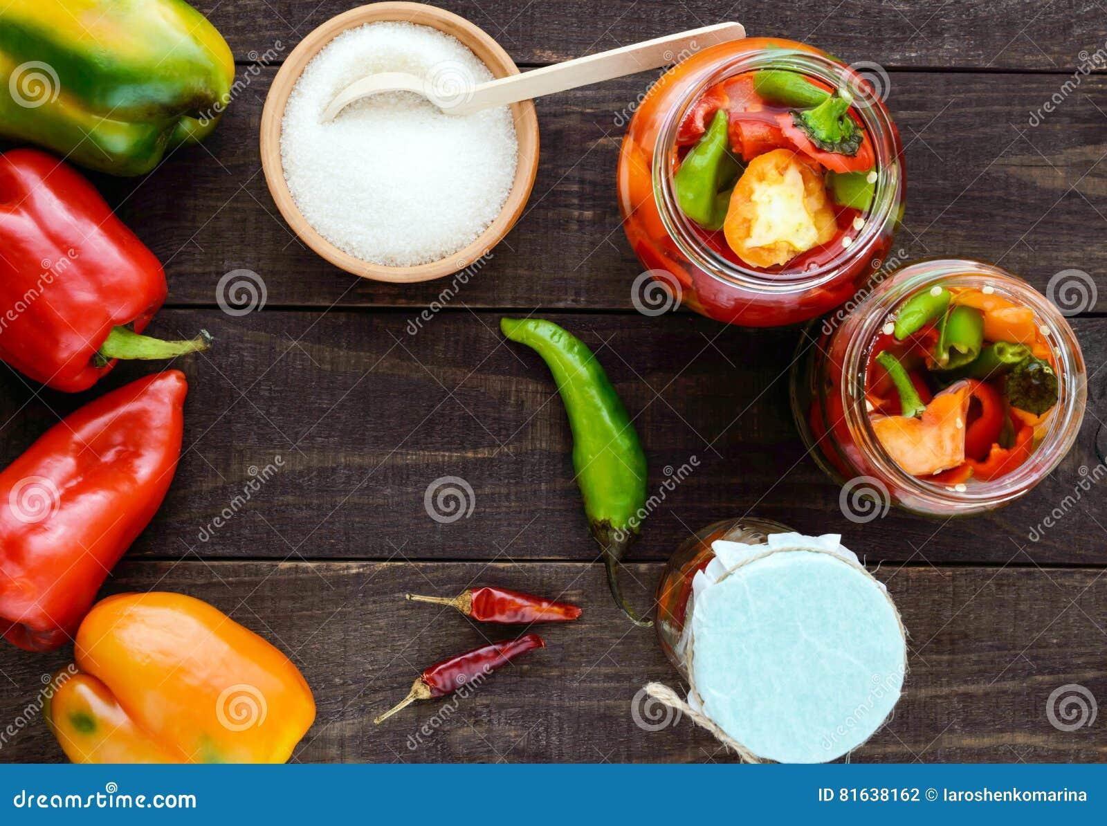 Marynowani warzywa w słoju szkło: gorąca czerwień i zieleni pieprze z cukierem