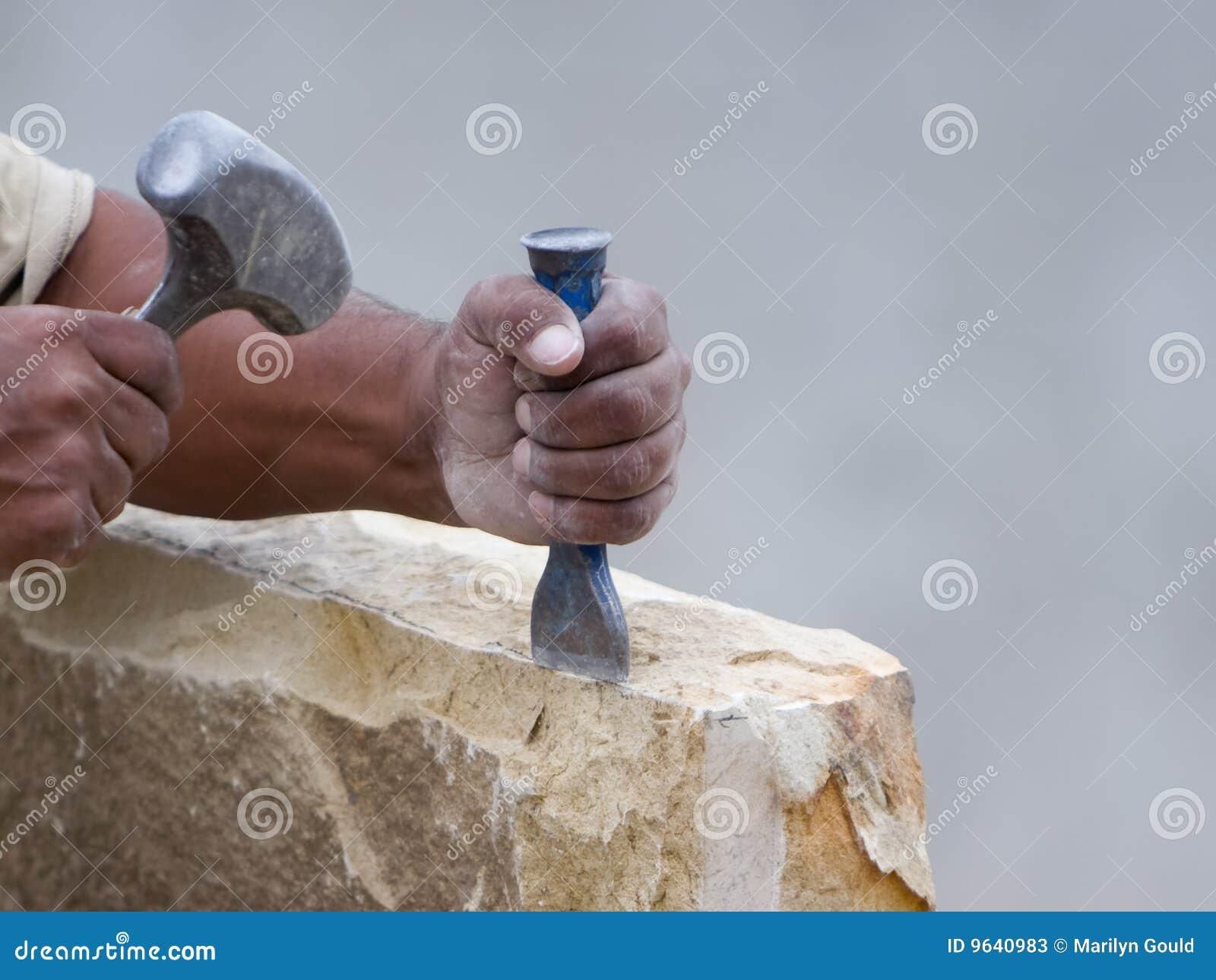 Masón de piedra que cincela un bloque de la piedra
