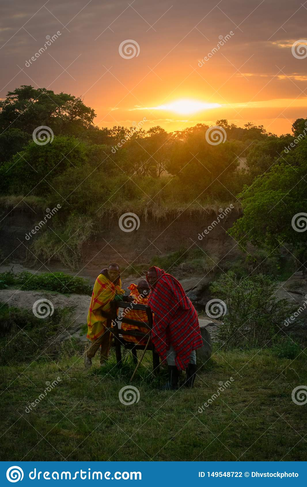 """Masai Mara, †de Kenya, África """"10 de agosto de 2018: Um grupo de homens do Masai na roupa tradicional que descansa no alvorecer"""