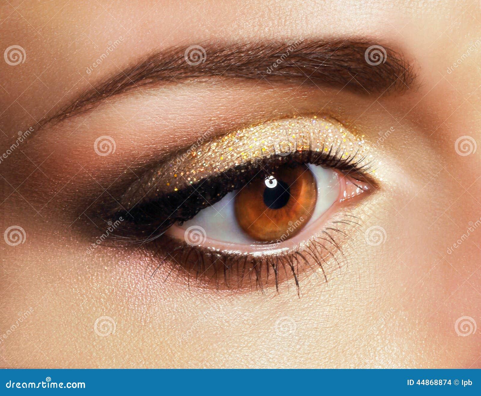 Mascara Slut upp kvinnas öga med guld- ögonskugga