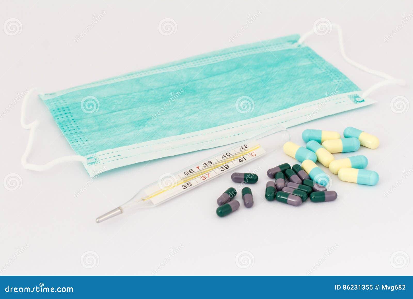 Mascarilla, termómetro de mercurio y diversas píldoras en la parte posterior del blanco