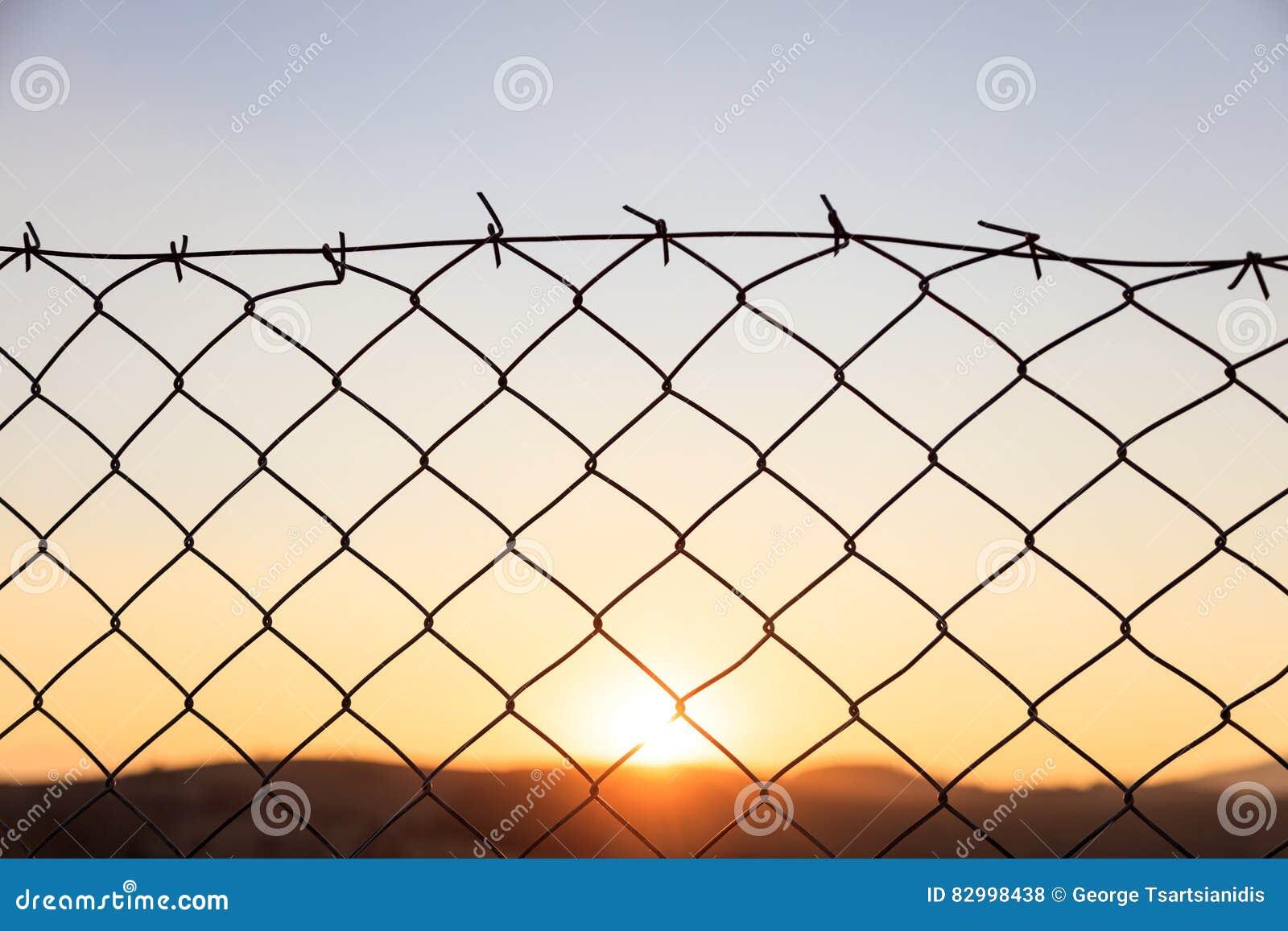 Maschendrahtzaun Auf Einem Sonnenunterganghintergrund Stockfoto ...