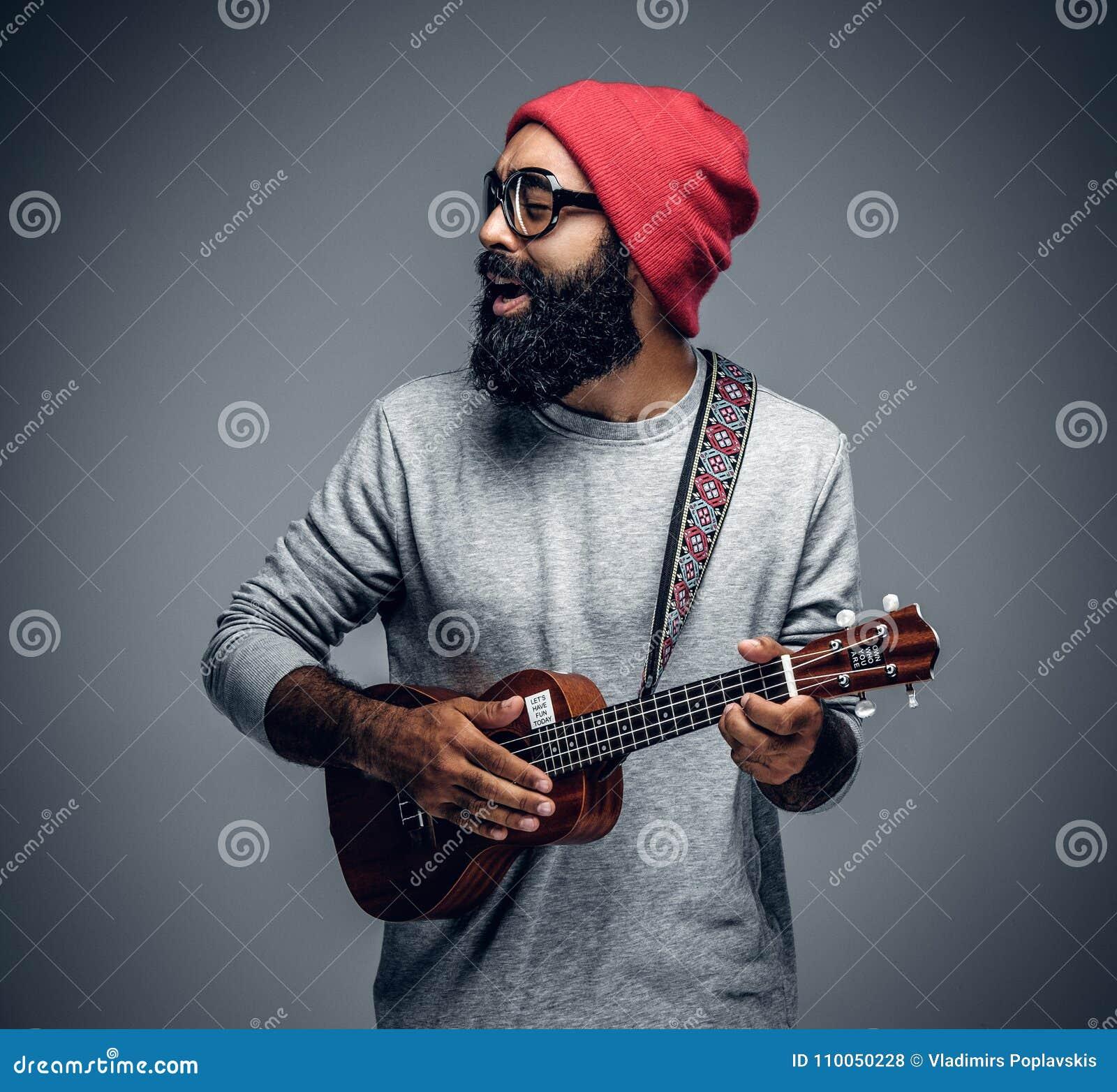 Maschio barbuto dei pantaloni a vita bassa in cappello rosso che gioca sulle ukulele