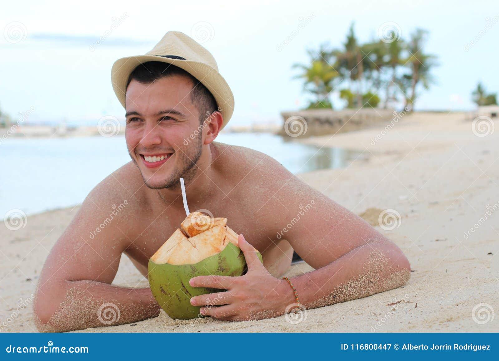 Maschio etnico che beve una noce di cocco fresca alla spiaggia