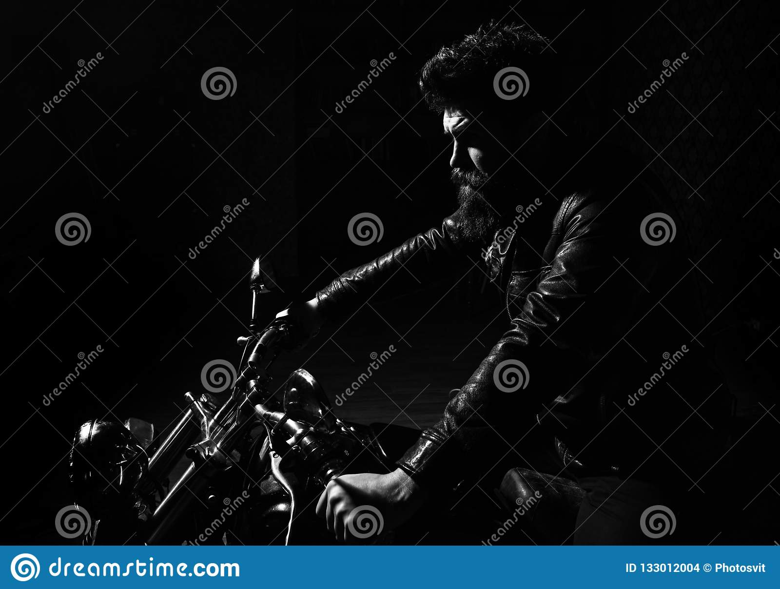 Masculinity concept. Man with beard, biker in leather jacket sitting on motor bike in darkness, black background. Macho