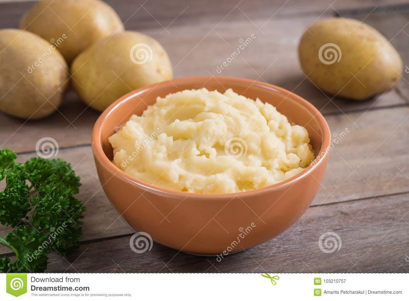Mashed potato in bowl and fresh potatoes on wooden table