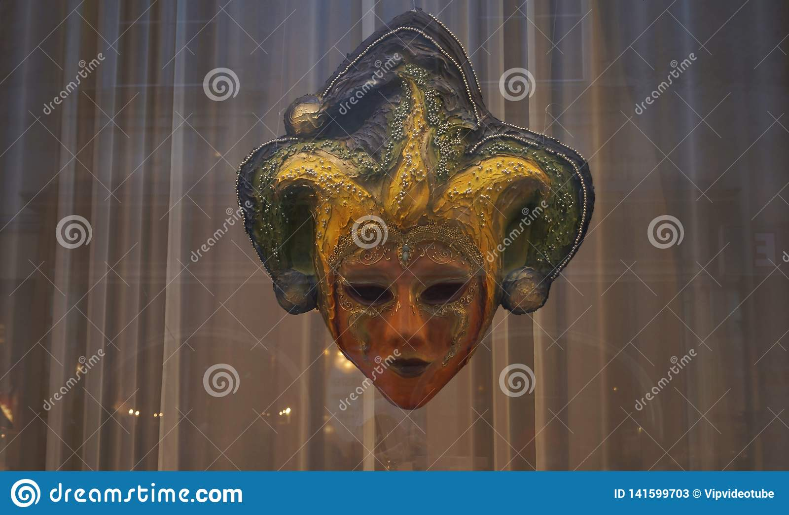 Mask of jester behind the glass