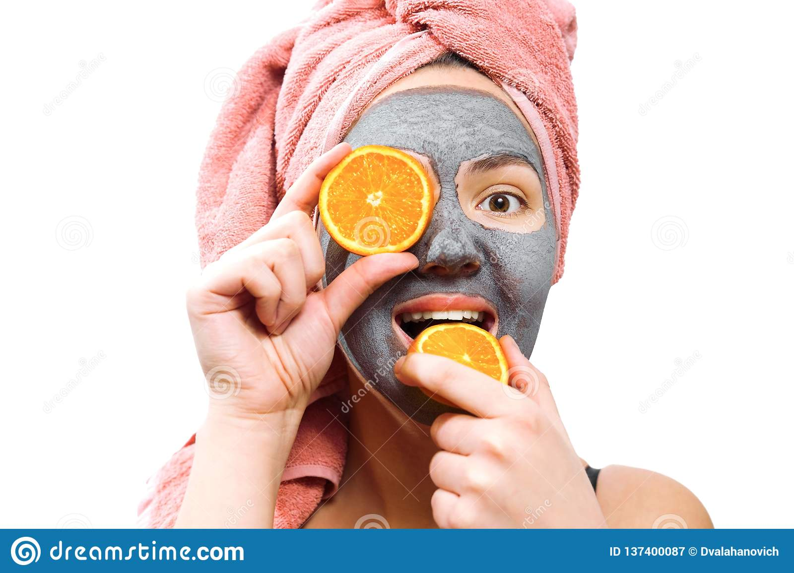 Mask for skin woman, happy and funny girl makes a mask for face skin, girl closes her eyes with orange, girl is smiling and bites