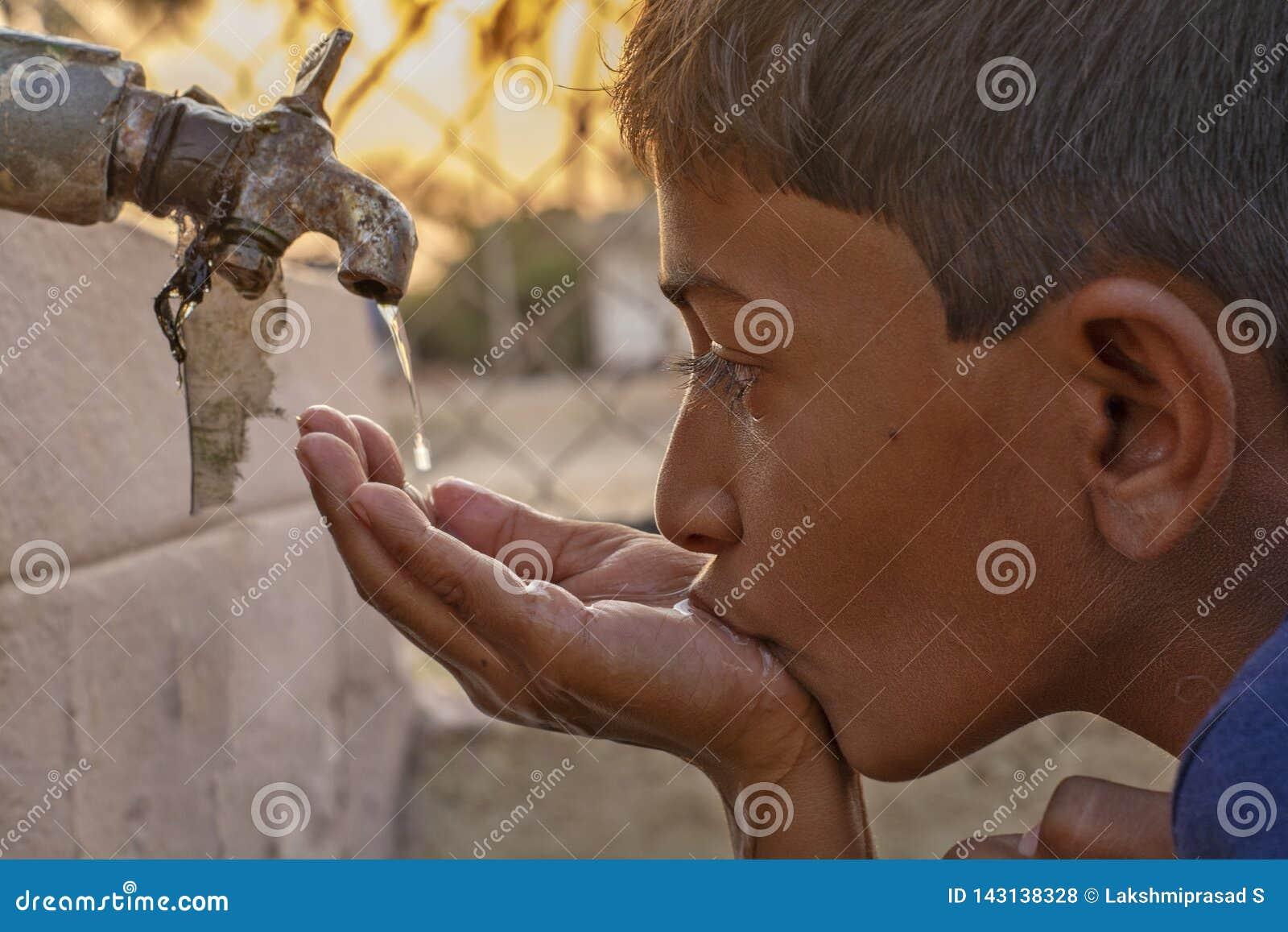 Maska, Karnataka, India - 26, Marzec 2019: Zbliżenie dziecko woda pitna bezpośrednio od korporacji wody kranowej w India