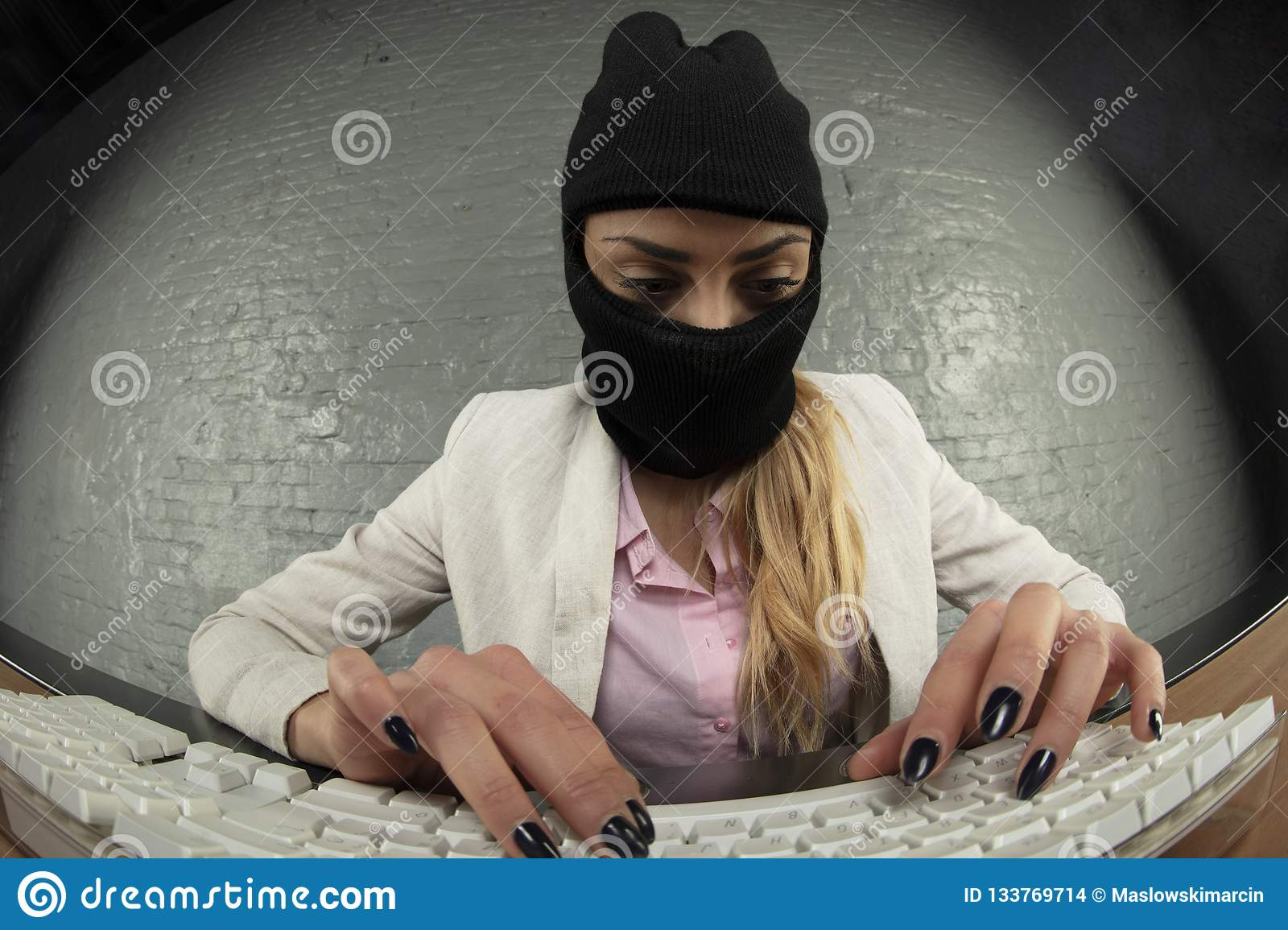 masked business woman steals data from a computer