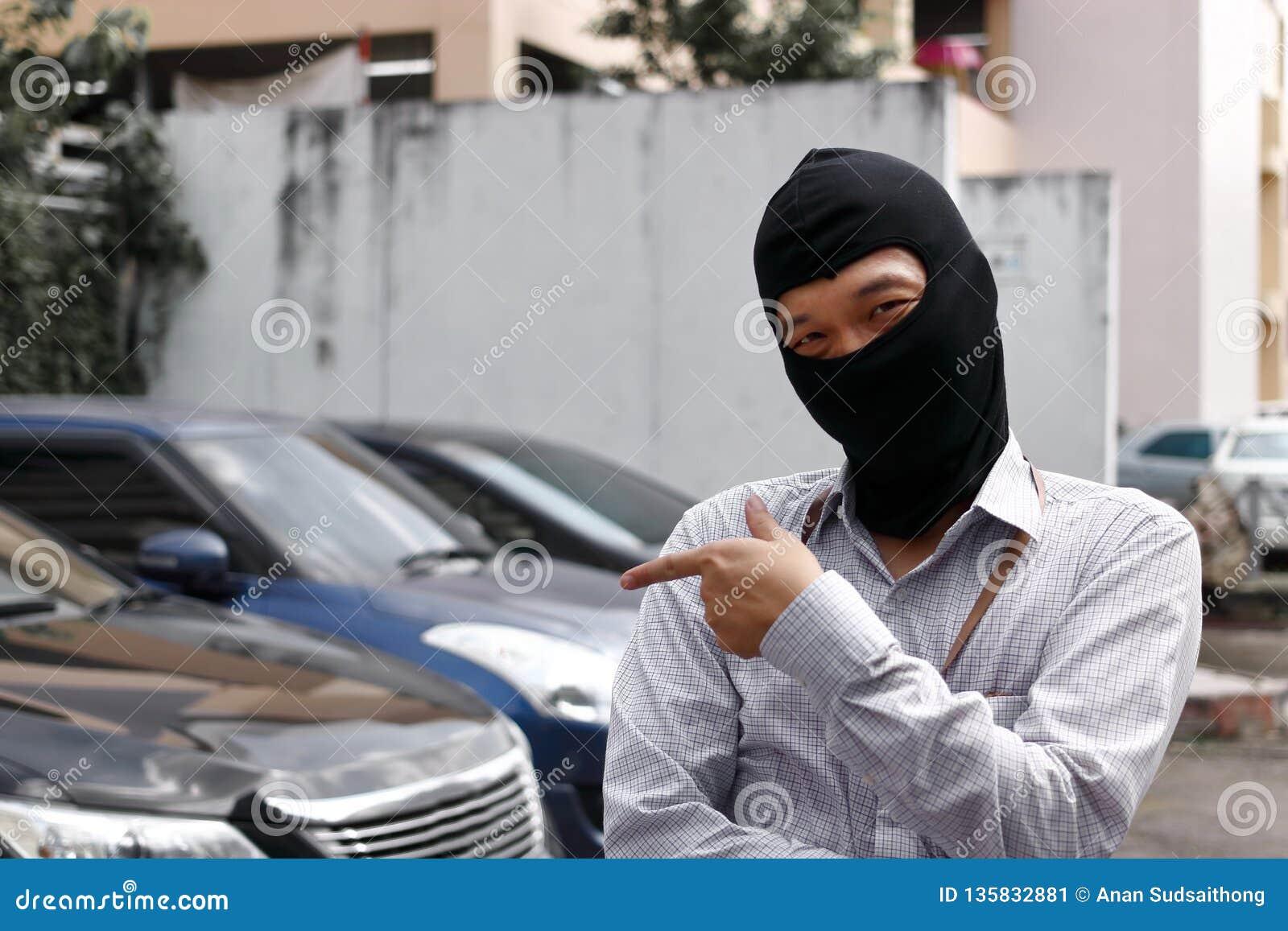 Maskerad tjuv i den svarta balaclavaen som försöker att bryta in i bilen