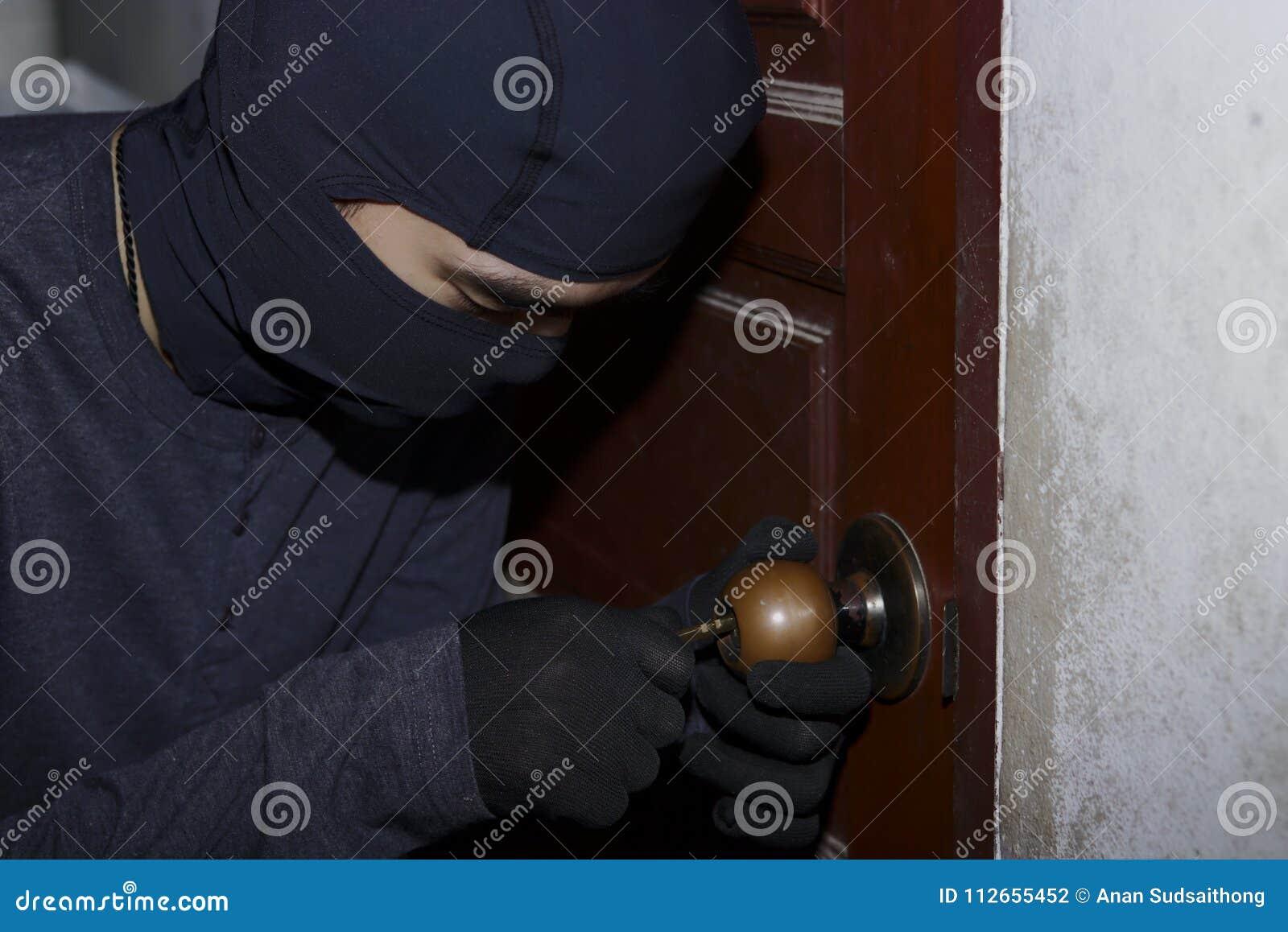 Maskerad tjuv med balaclavaen som skriver in och bryter in i ett hus på nattetid vägg för skugga för pistol för holding för brott