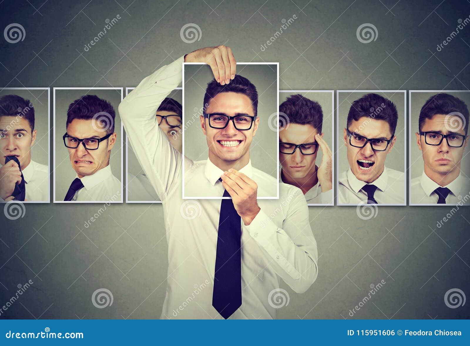 Maskerad ung man i exponeringsglas som uttrycker olika sinnesrörelser