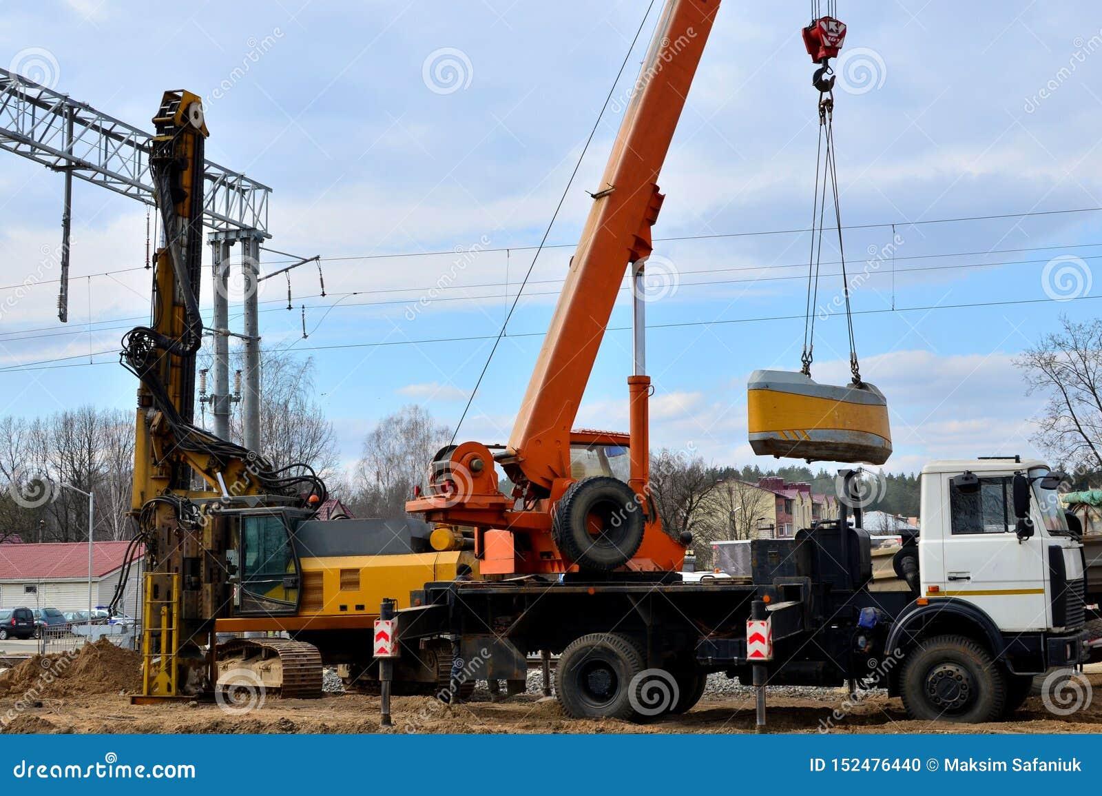 Maskin för fundamenthögborrande och mobil kran på konstruktionsplatsen