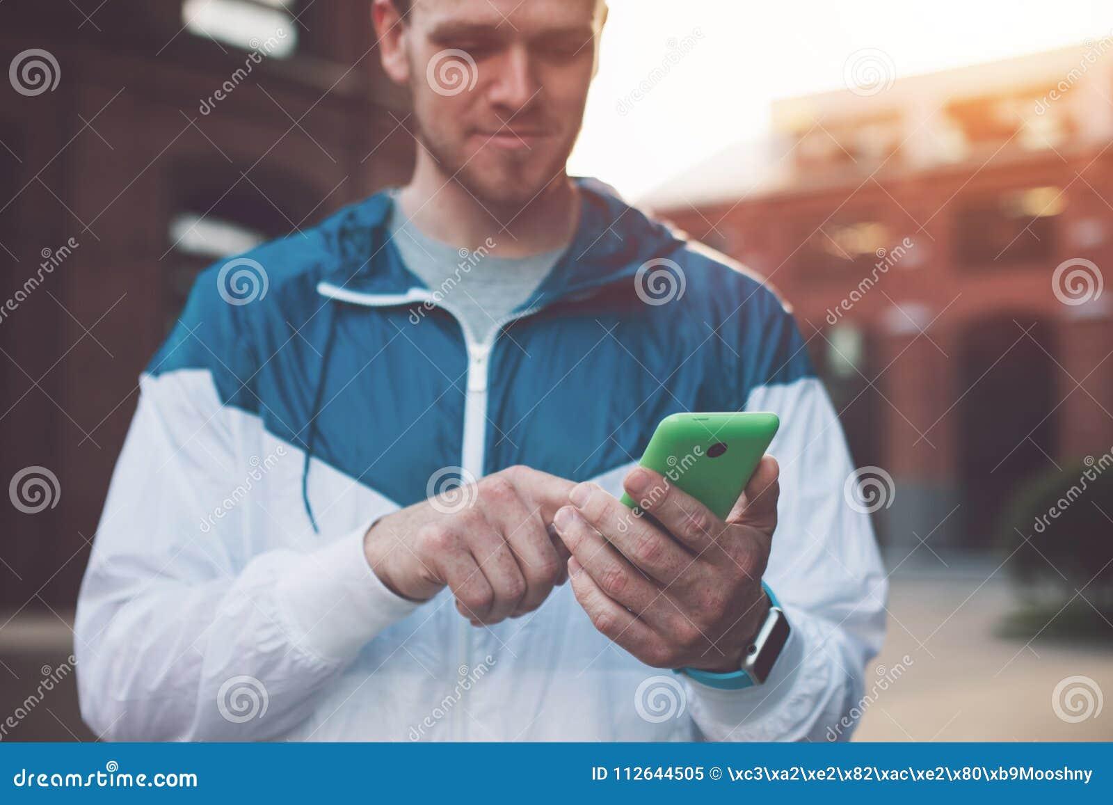 Maskinskrivningmeddelande för ung man på hans mobiltelefon, solnedgång på gatan