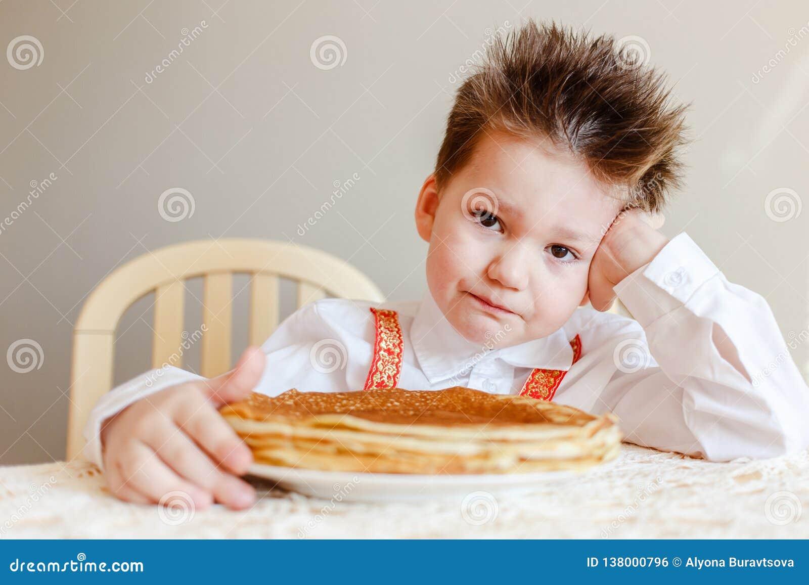 Maslenitsa russe le garçon s assied à une table avec un plat des crêpes frites Crêpes le Mardi gras