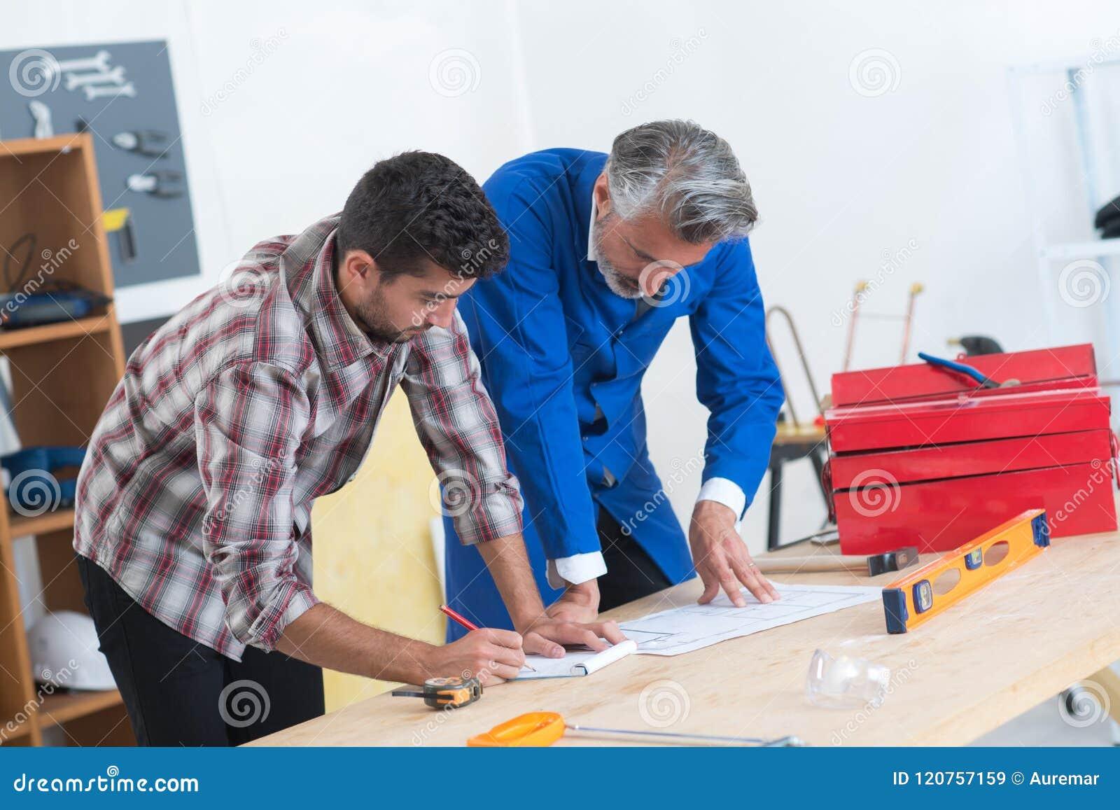 Mason and engineer measuring plans