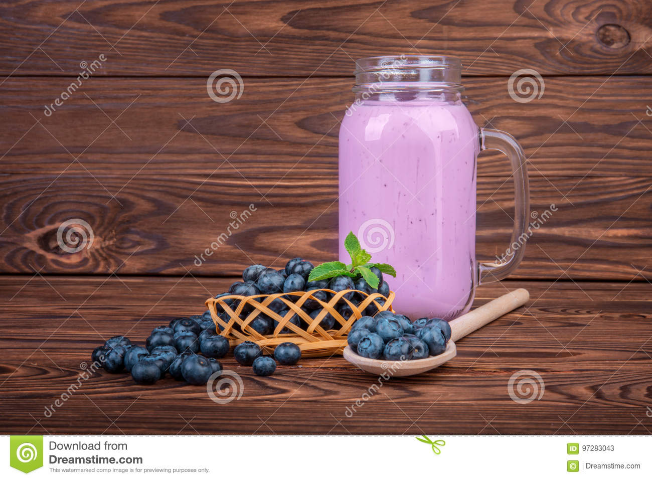 A mason jar filled with fresh blueberry smoothie on a wooden background. A heap of bright ripe berries near a full can of berry yo