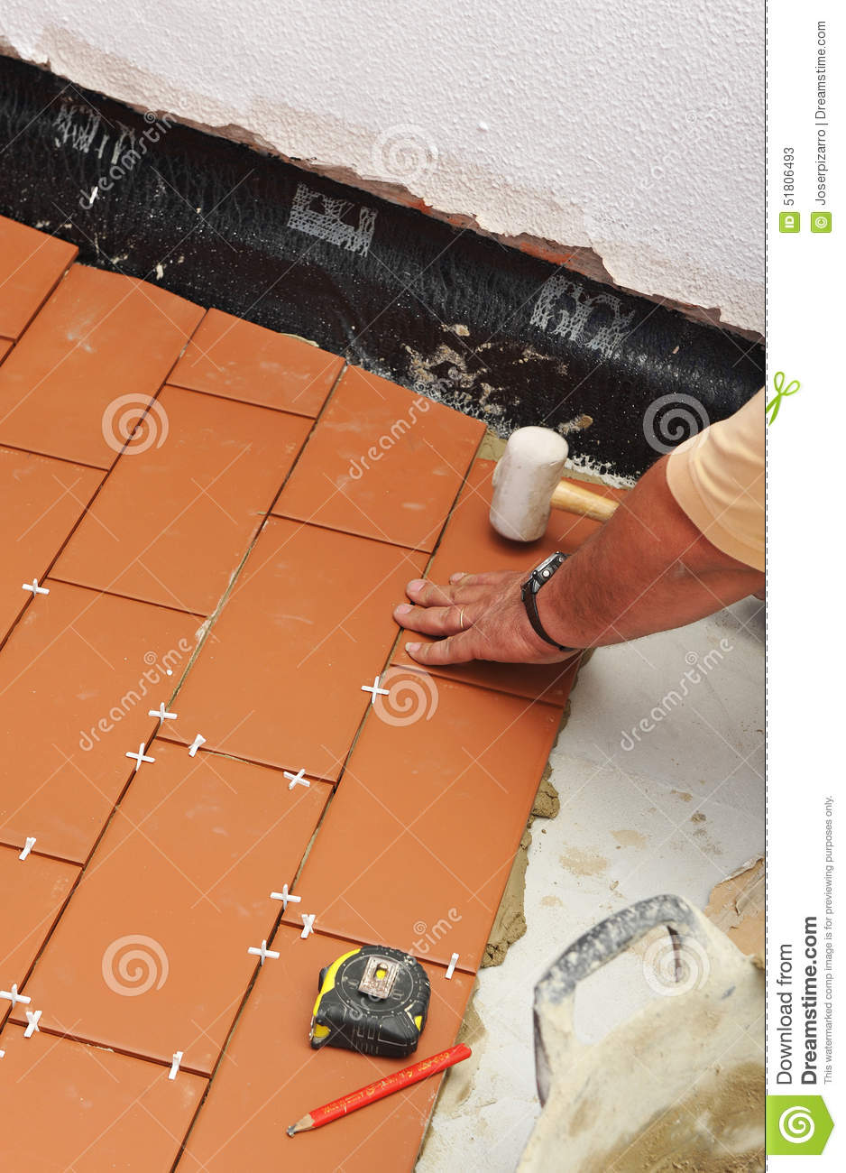 Working With Ceramic Tile : Mason paving the floor of courtyard a house with