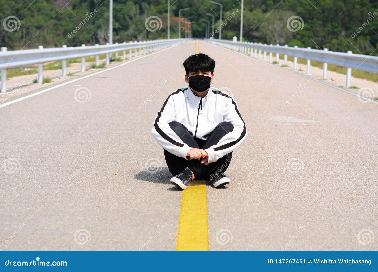 Masque de port de garçon détendre sur la route après avoir pulsé